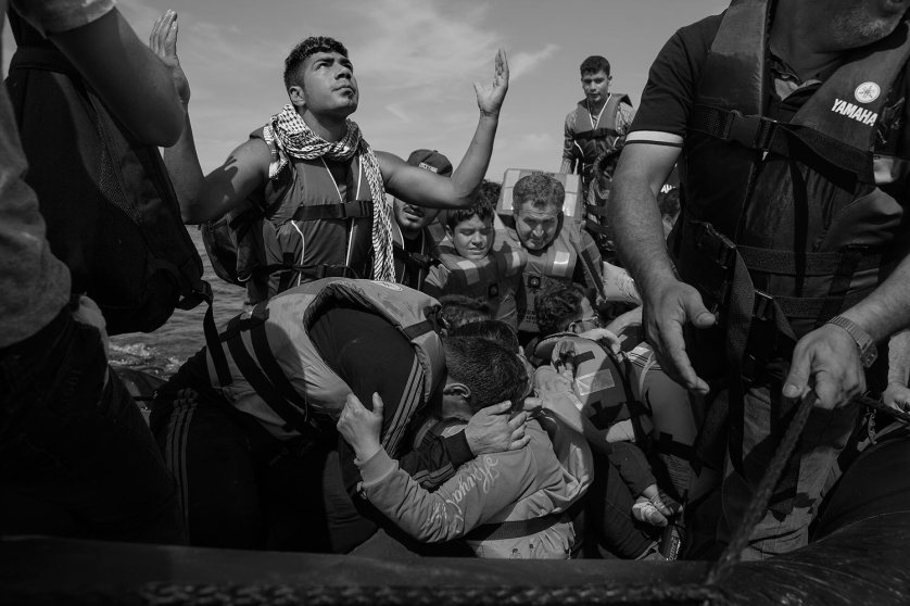 Refugees celebrate after arriving on the beach in Lesbos, Greece. Thousands of migrants each day set out from nearby Turkey for the Greek island, riding in barely seaworthy rubber boats. Some don't make it, September 26, 2015.James Nachtwey for TIME