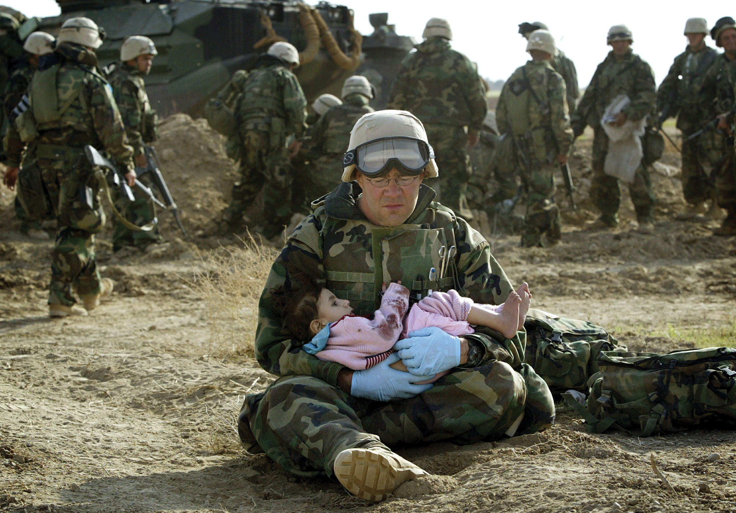 U.S. Navy Hospital Corpsman HM1 Richard Barnett, assigned to the 1st Marine Division, holds an Iraqi child in central Iraq, March 29, 2003.  Confused front line crossfire ripped apart an Iraqi family after local soldiers appeared to force civilians towards positions held by U.S. Marines.