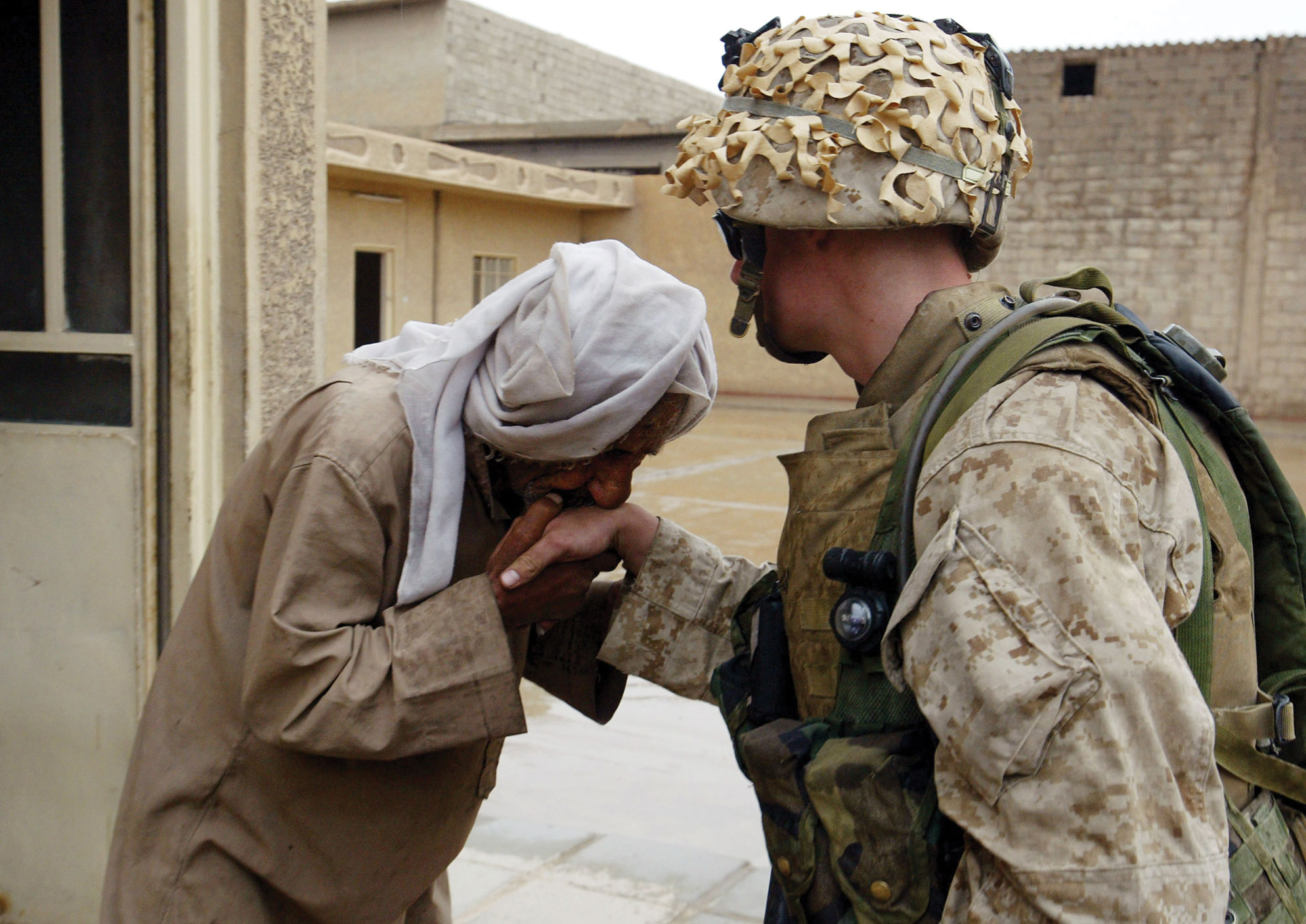 An Iraqi civilian kisses the hand of U.S. Marine Cpl. Joseph Sharp from Peoria, Ill., after Marines from the 1st Battalion 5th Marines gave him a supply of food and water in Fallujah, Iraq, Monday, April 19, 2004.