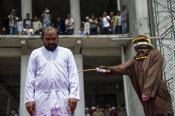 An Indonesian Shari'a police whips a man during a public caning ceremony outside a mosque in Banda Aceh, capital of Indonesia's Aceh province, on Sept, 18, 2015
