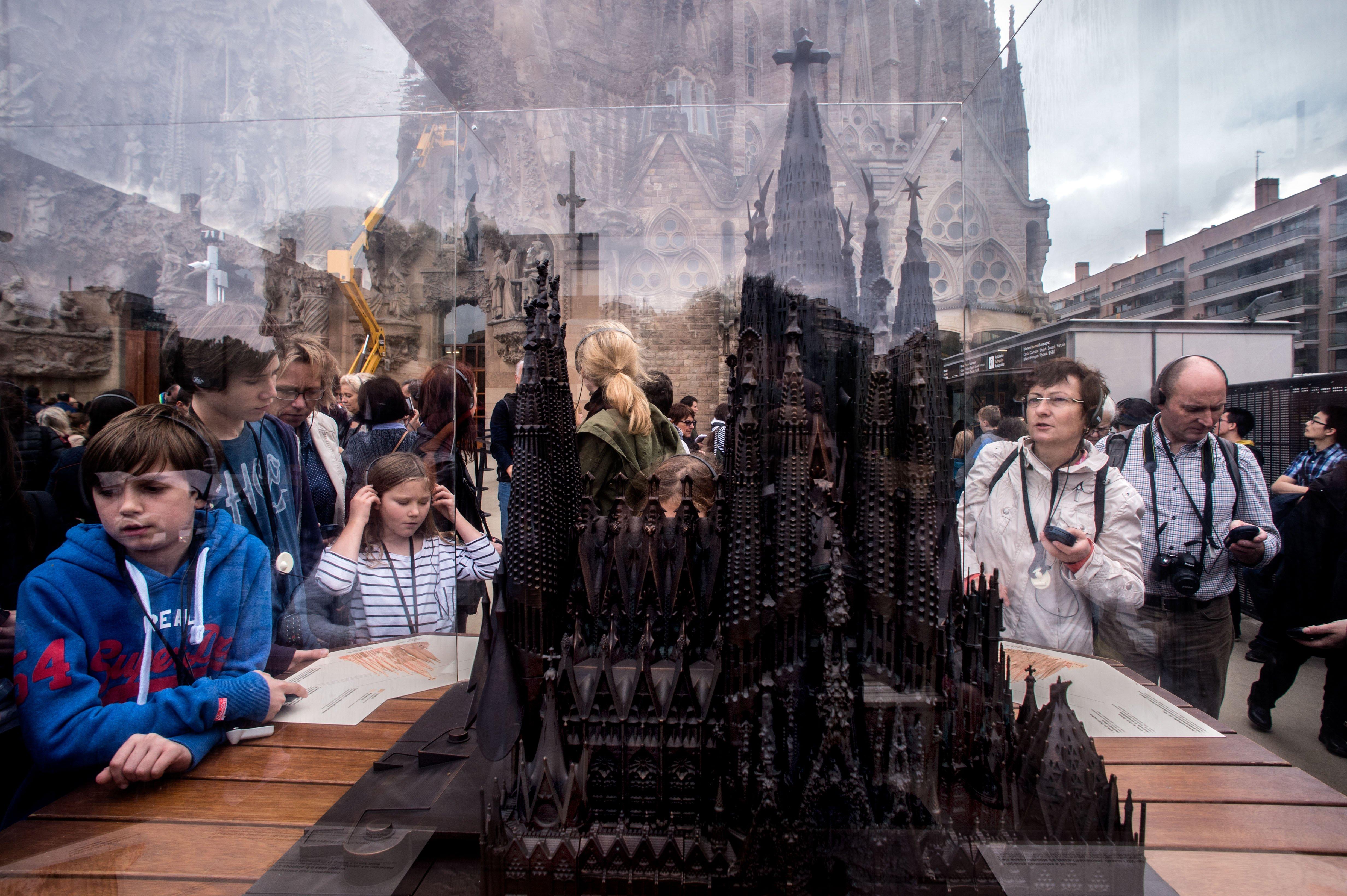 Tourists look at a mockup of 'La Sagrada Familia' as they visit the temple in Barcelona on Oct. 26, 2015.