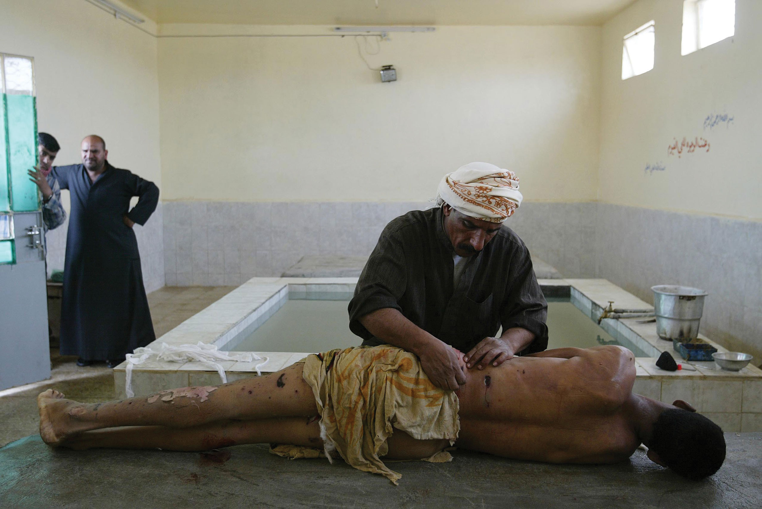 Ali Hadi, a professional body washer, prepares the body of a bombing victim for Muslim burial as the man's relatives watch in Najaf, Iraq, on March 3, 2004.