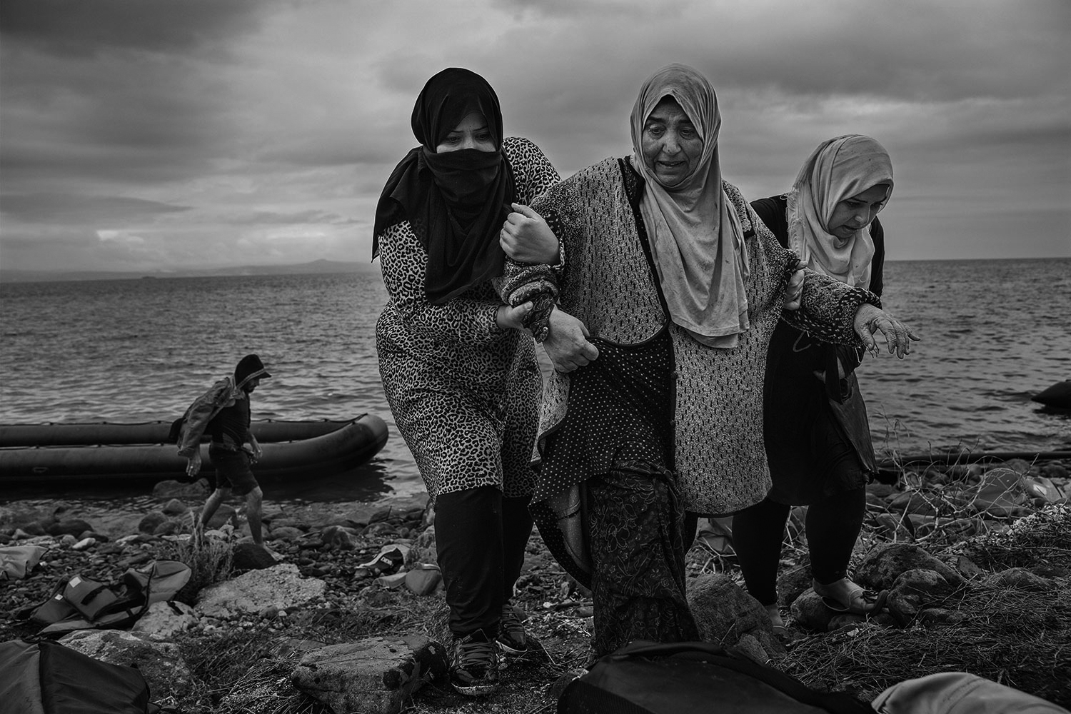 Two women help a third scramble ashore after arriving on the beach in Lesbos, Greece, Sept. 23, 2015.