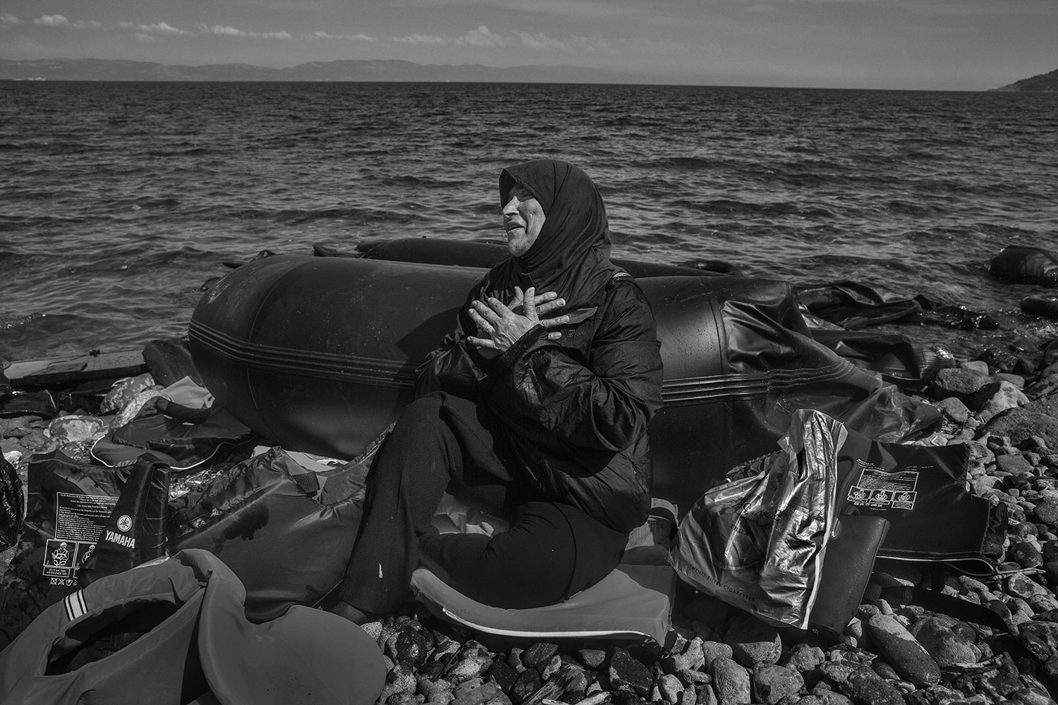 Leaving behind everything they've ever known, migrants arrive on the beach in Lesbos, Greece with little or no possessions. A woman sits on the beach recovering  from the sea journey, Sept. 27, 2015.