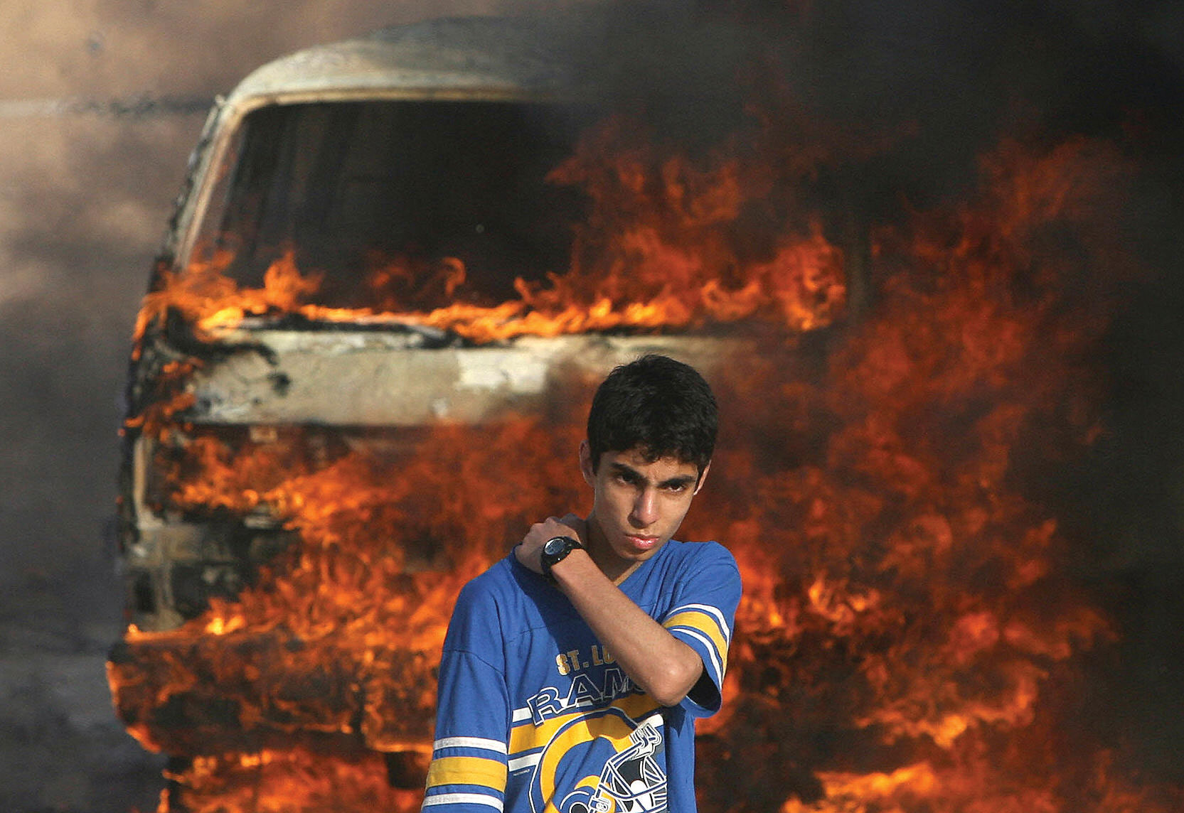 A Palestinian youth stands in front of a burning vehicle during clashes between rival Fatah and Hamas gunmen in Gaza City, May 14, 2007.