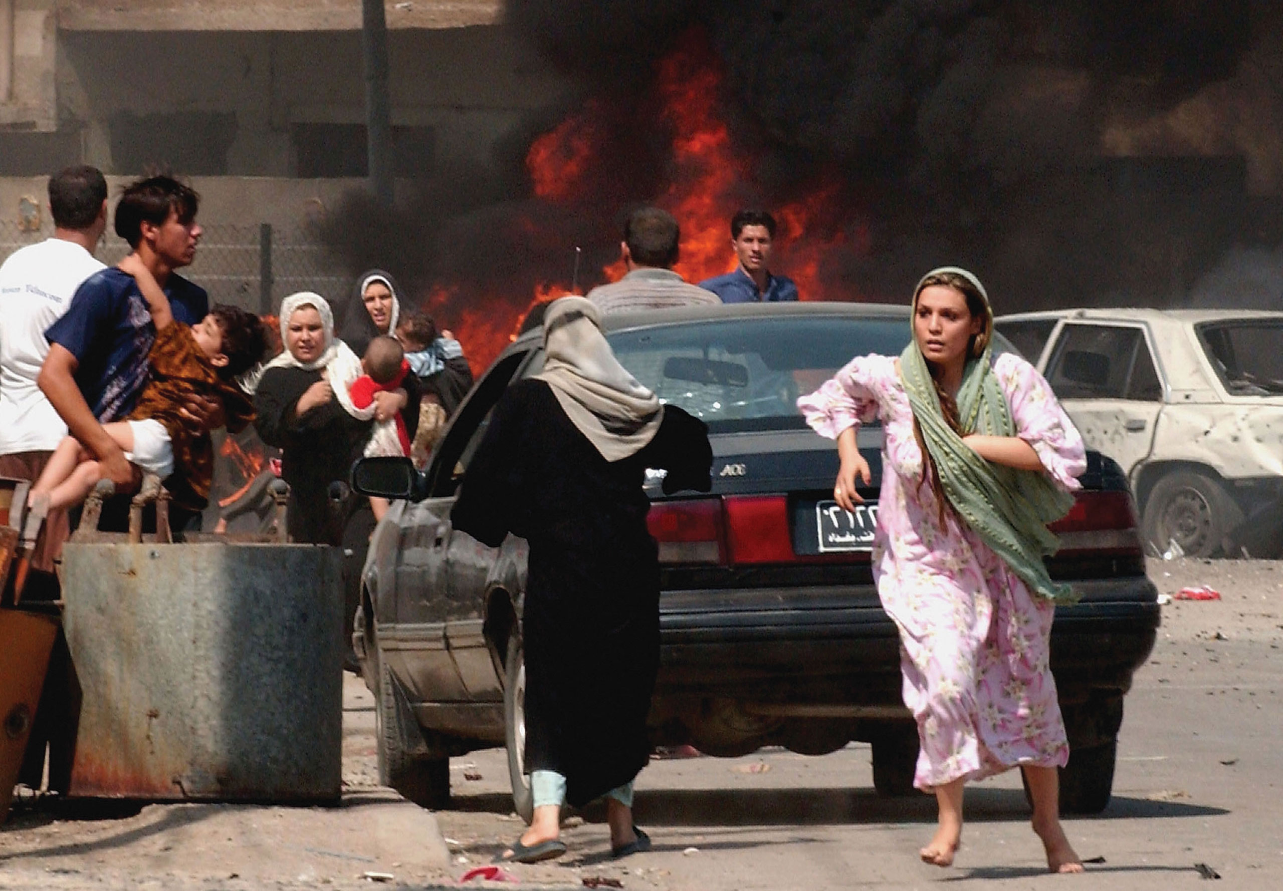 Iraqi citizens flee the scene after three separate explosions targeted a U.S. military convoy during the opening ceremony of a sewage station. The explosions killed at least 35 people and wounded more than 100 others, according to Iraqi police. Baghdad, Iraq, Sept. 30, 2004.