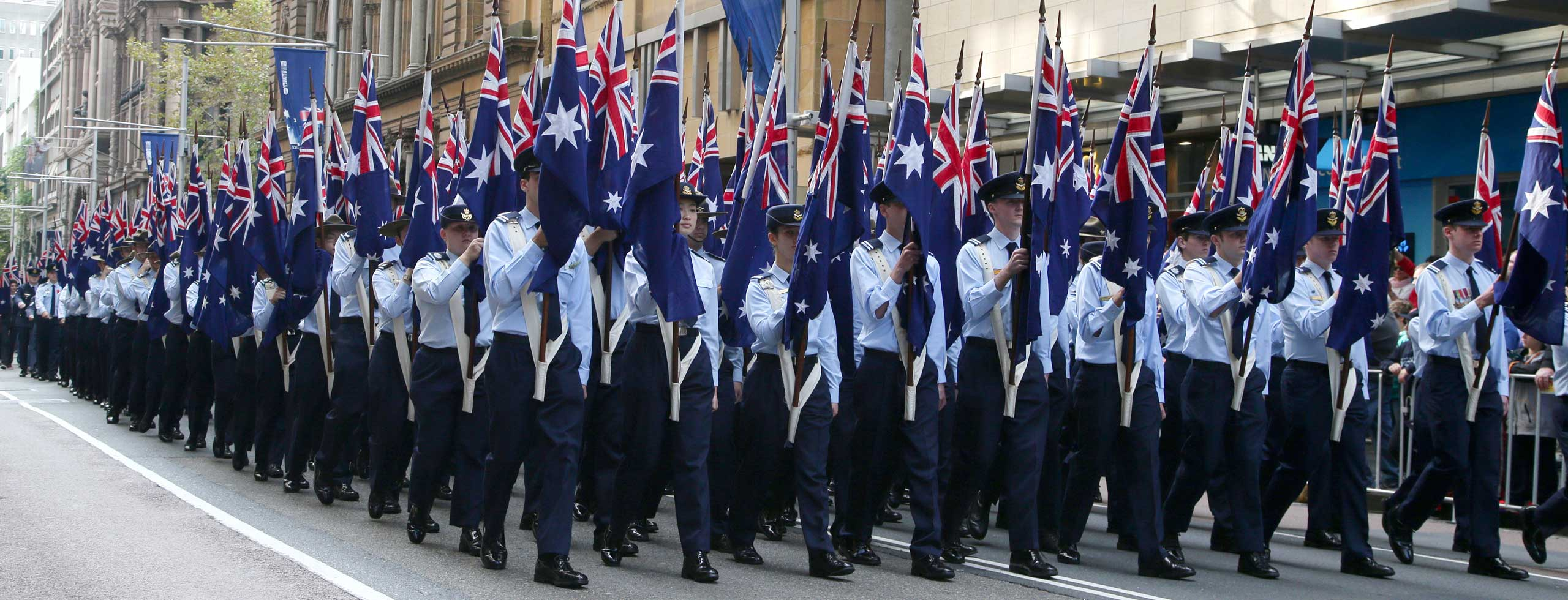 Air Force cadets carrying National flags march during an ANZAC Day parade in Sydney, April 25, 2015.