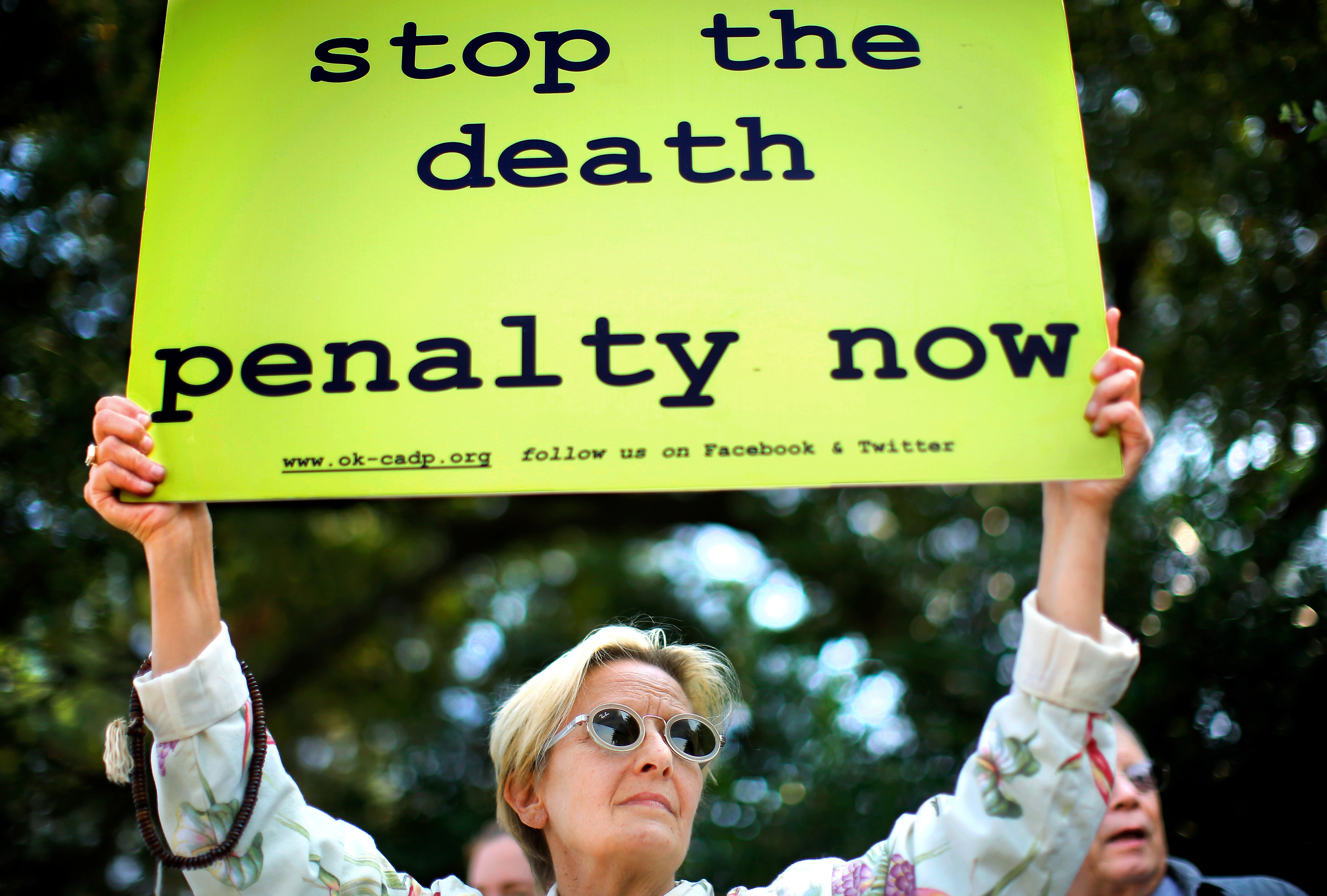 Karin Stafford joins a crowd of protesters in front of the governor's mansion in Oklahoma City, Okla., Sept. 30, 2015.