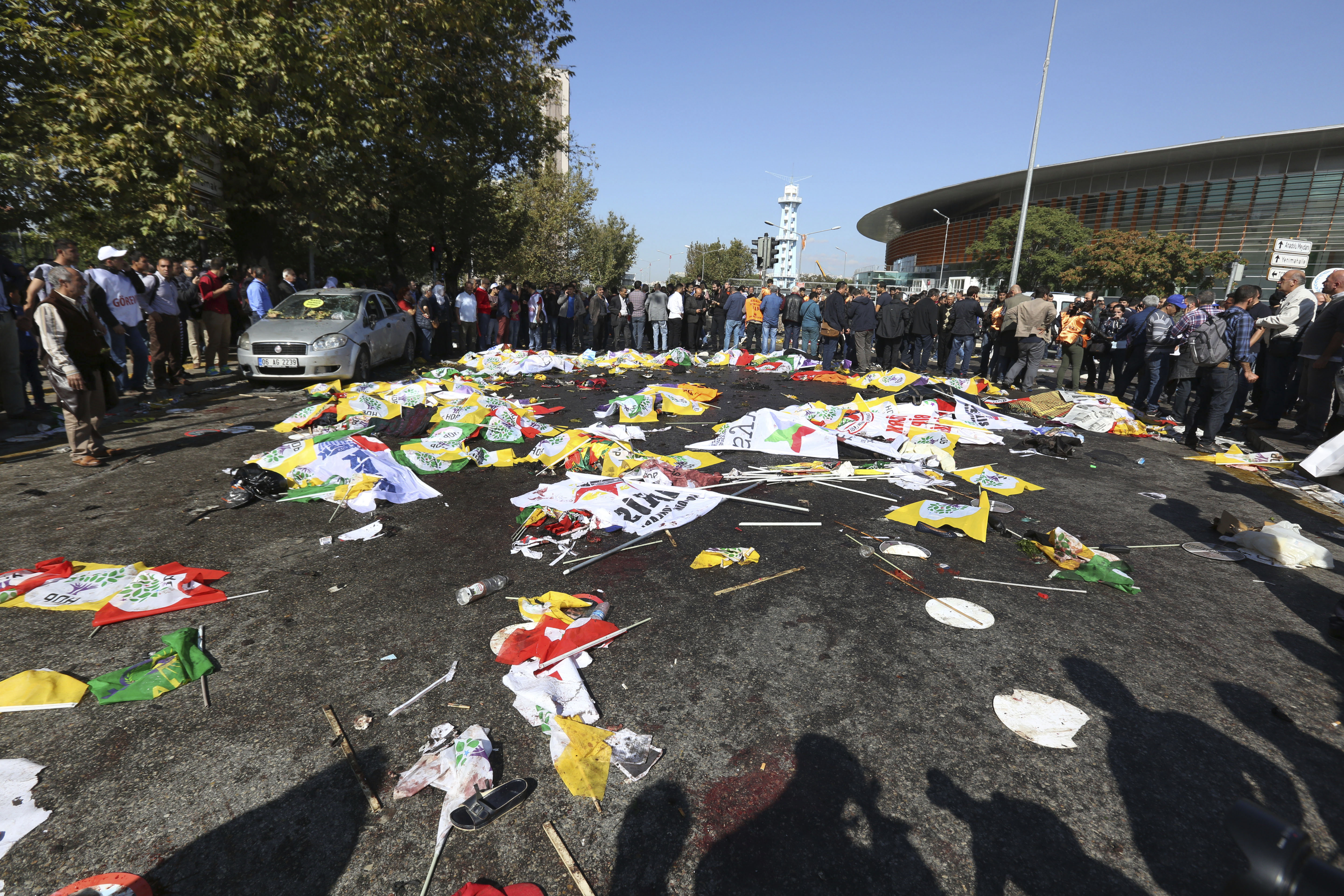People surround the area where bodies of victims are covered with flags and banners at the site of an explosion in Ankara, Turkey, on Oct. 10, 2015.