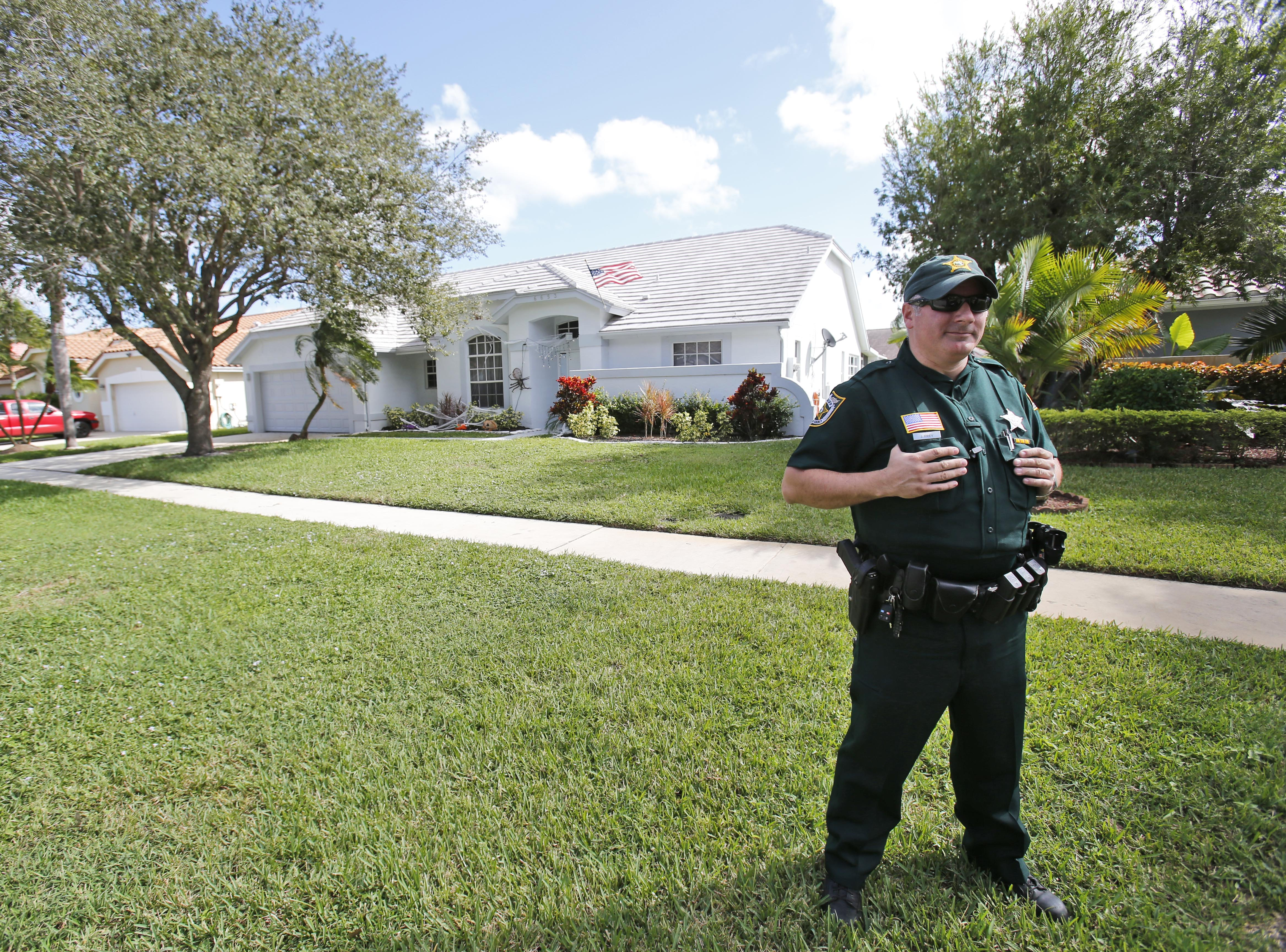 A Palm Beach County Sheriff's deputy keeps watch over the home of Palm Beach Gardens police Officer Nouman Raja, in Lake Worth, Fla., on Oct. 21. 2015.