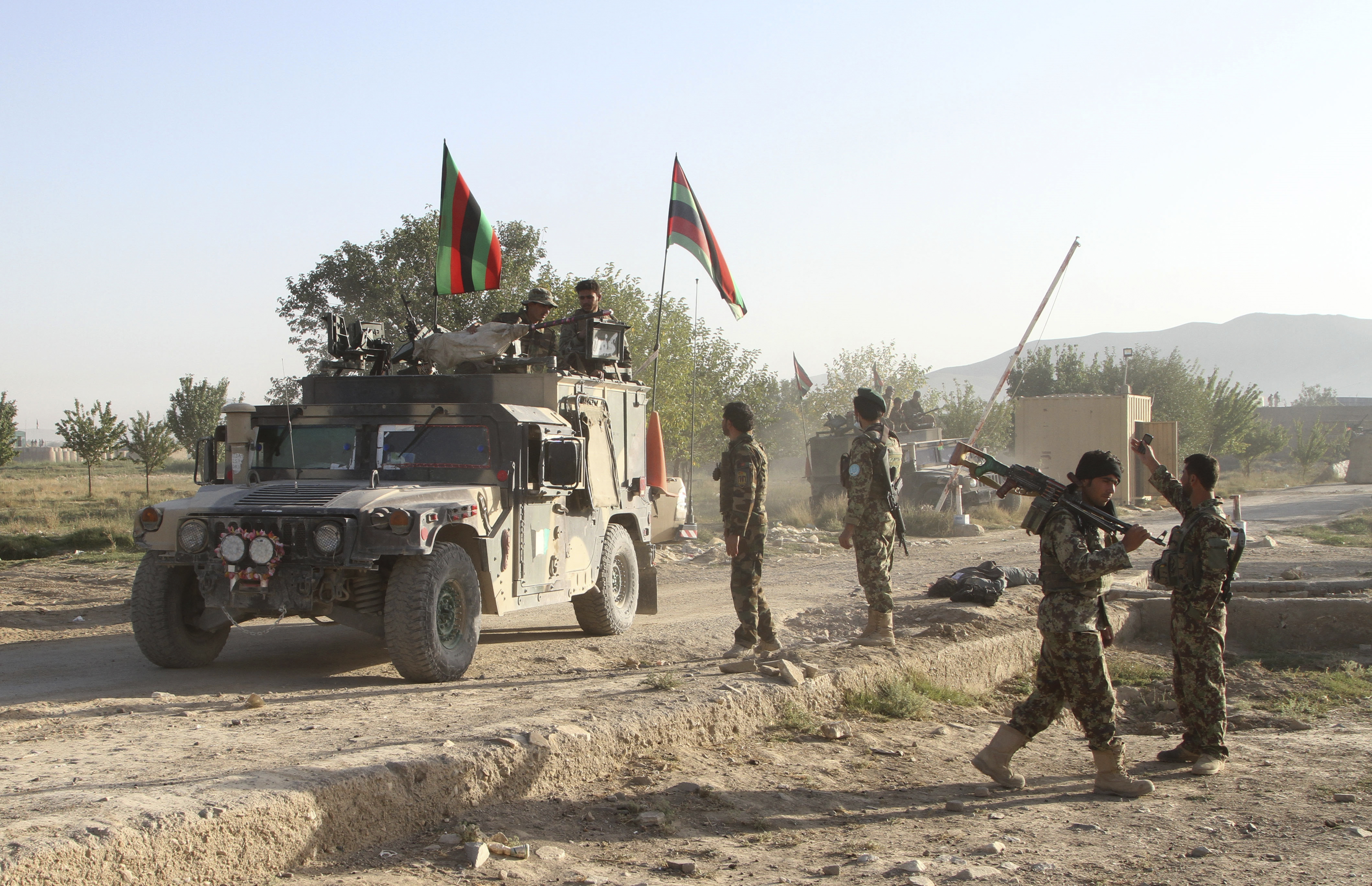 Soldiers with the Afghan national army stand guard near the dead body of a Taliban attacker in front of the main prison building after an attack in Ghazni province, eastern Afghanistan, Monday, Sept. 14, 2015.