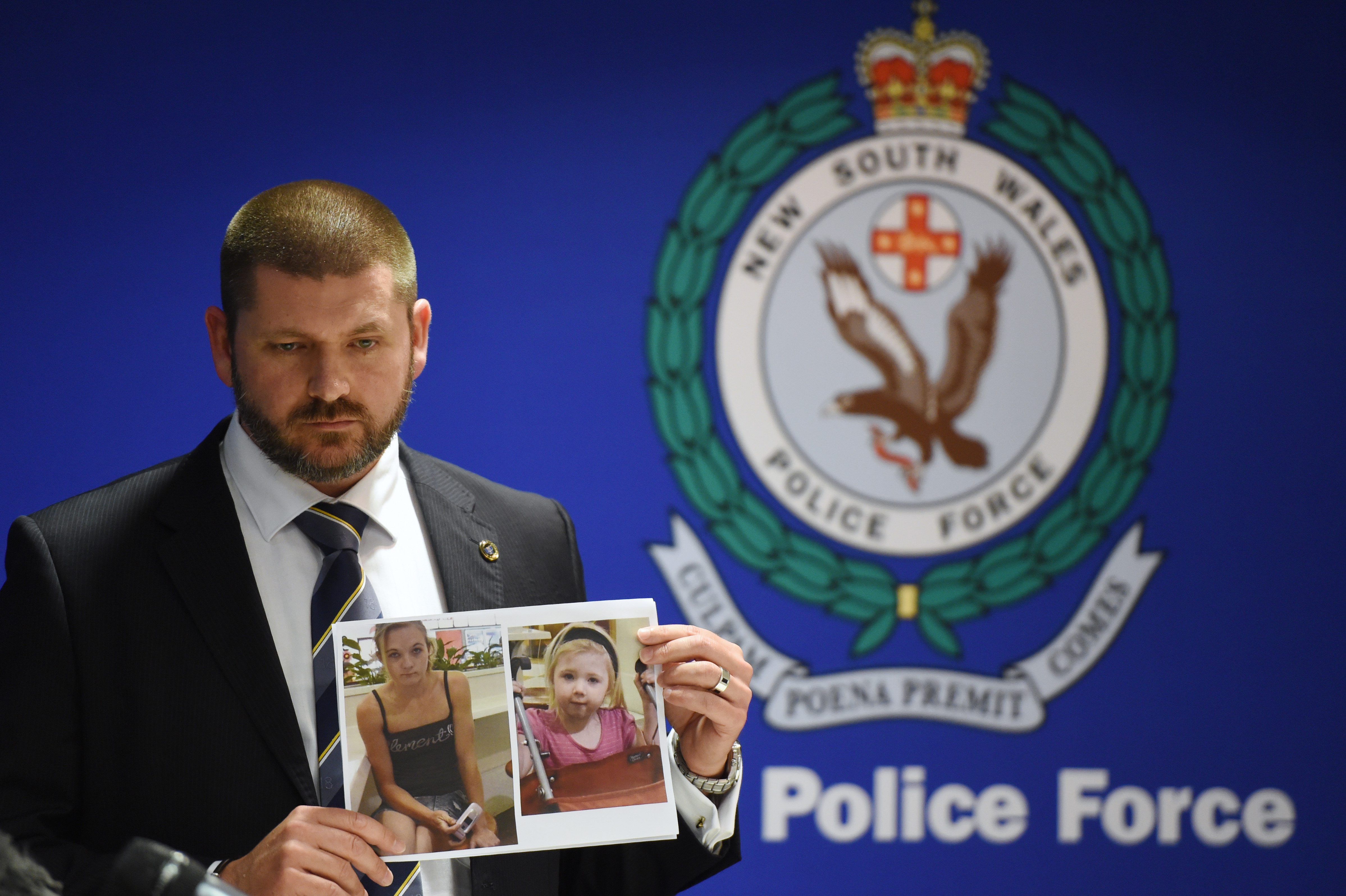 Police Detective Inspector Jason Dickinson holds up a photo of Karlie Jade Pearce-Stevenson and her daughter Khandalyce Kiara Pearce, during a press conference in Sydney, Wednesday, Oct. 21, 2015