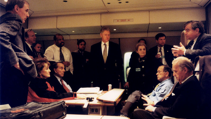 Bill Clinton (center) aboard Air Force One en route to Bosnia, with Madeline Albright (middle right), Joe Biden (far right), Bob Dole (left), Elizabeth Dole (far left) and Ted Stevens on Dec. 22, 1997.