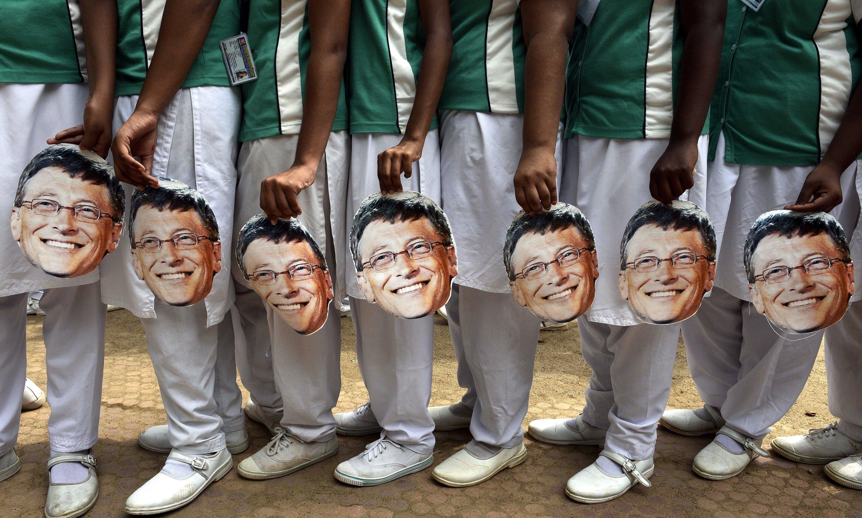 Indian schoolchildren hold Bill Gates masks.