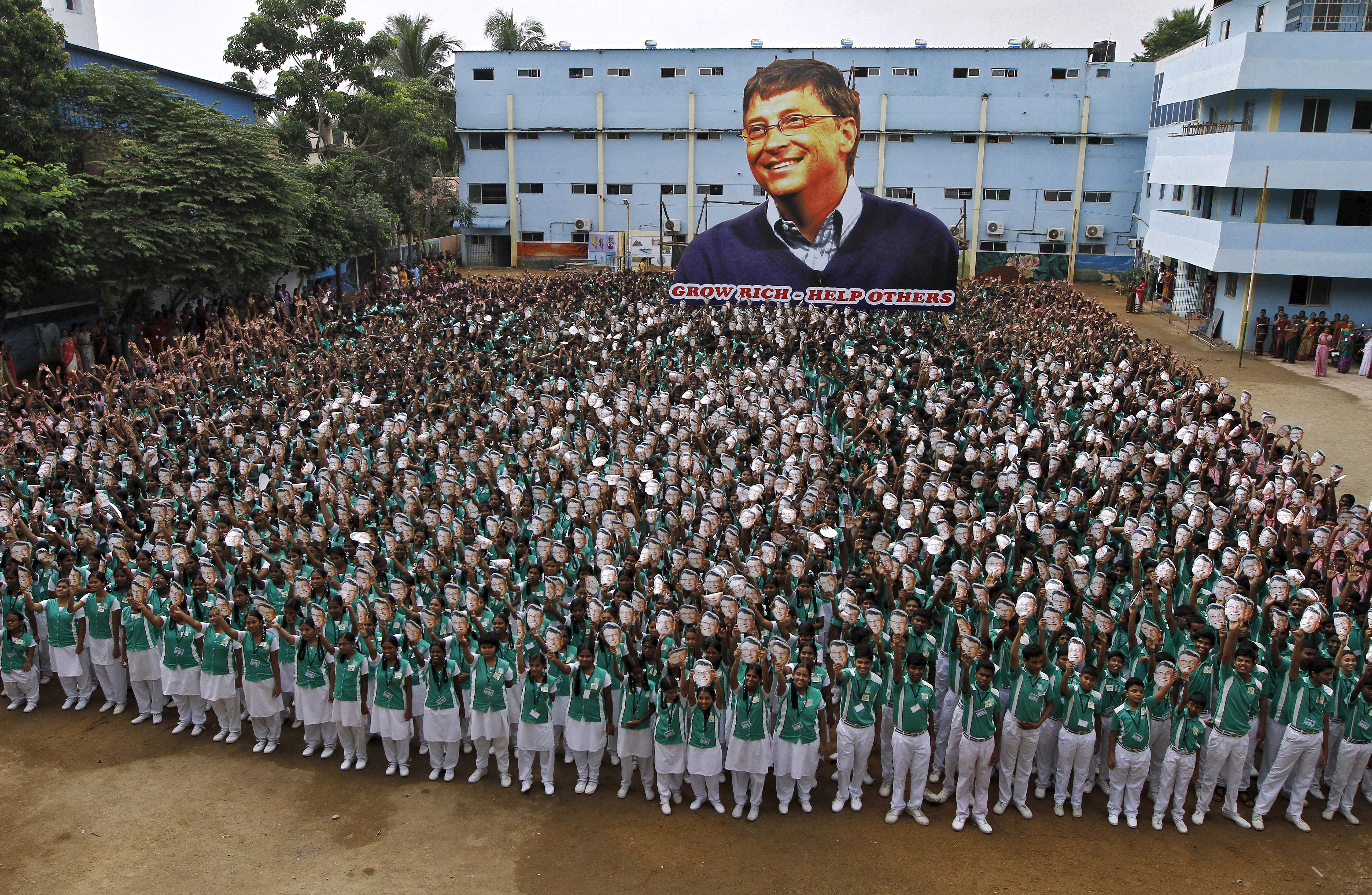 School children hold portraits of Microsoft co-founder Bill Gates in front of a giant picture of Gates during celebrations to mark his 60th birthday inside the school premises in Chennai, India on Oct. 28, 2015.
