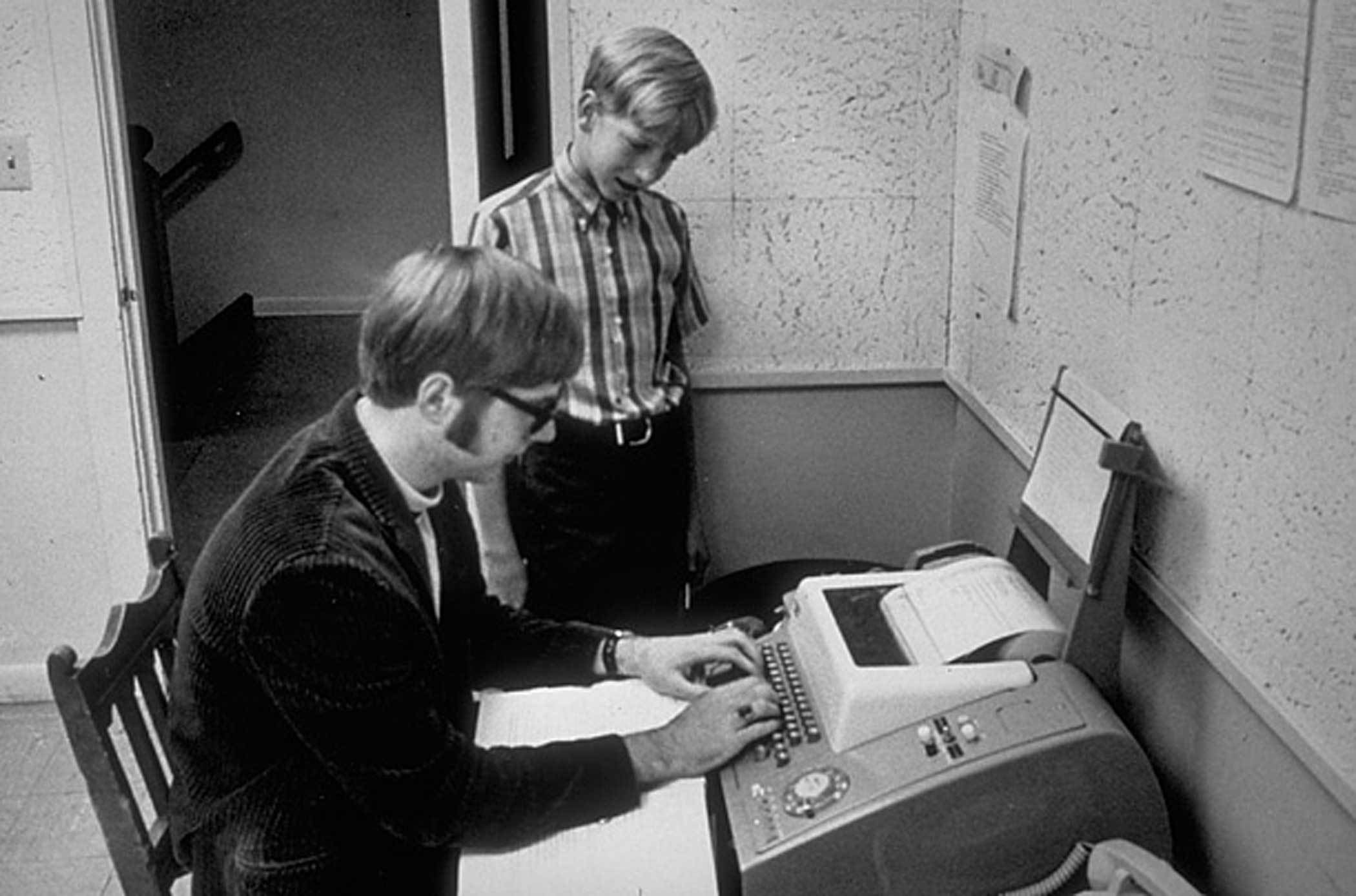 Gates watches his friend and future Microsoft co-founder Paul Allen typing on a teletype terminal at the Lakeside School in Seattle in 1968. Gates was 13 when he entered the exclusive prep school, which was around the time this photo was taken.