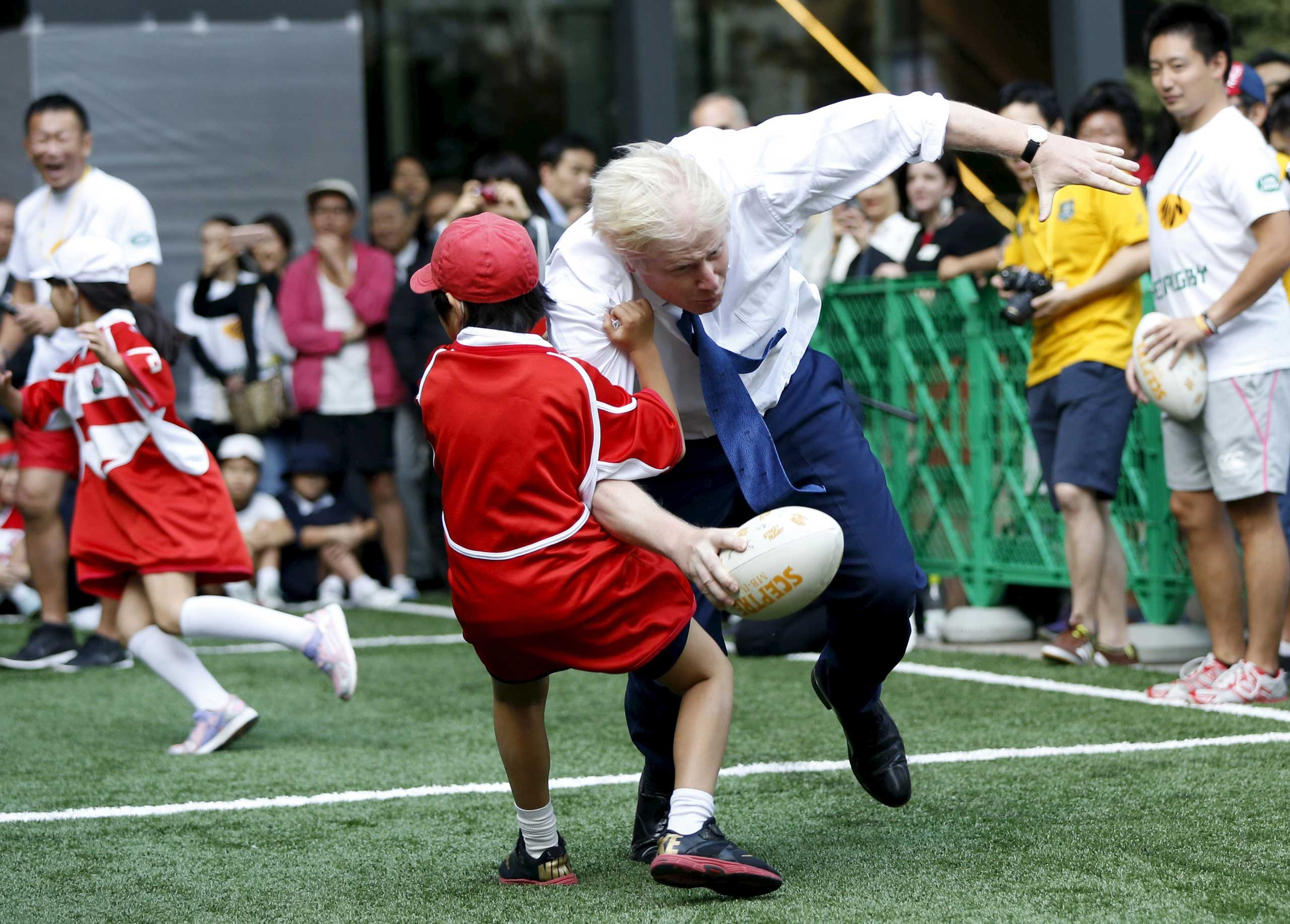 London's Mayor Boris Johnson collides with 10-year-old Toki Sekiguchi during a game of Street Rugby with a group of Tokyo children, outside the Tokyo Square Gardens building, on Oct. 15, 2015.