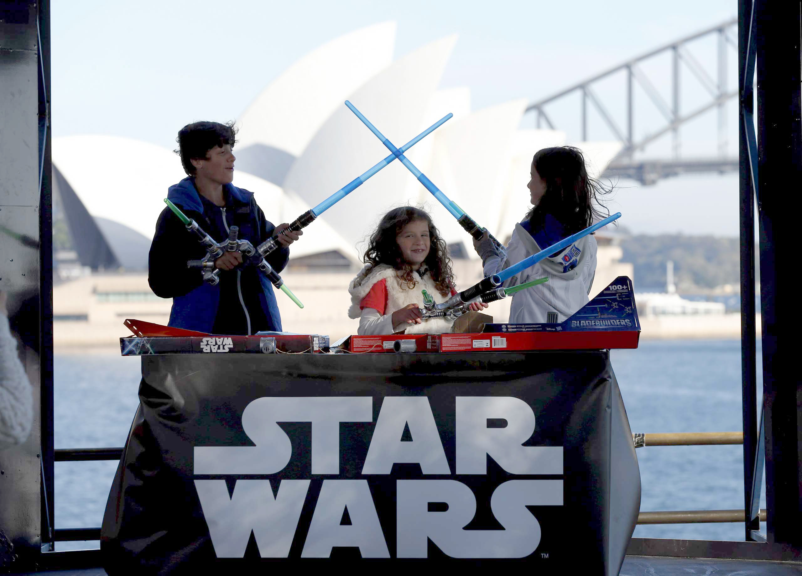 Caleb (L-R), Kayley and Annie Bratayley from the United States participate in a live internet unboxing event to reveal new light saber toys from the film  Star Wars - The Force Awakens  in Sydney, Sept. 3, 2015.