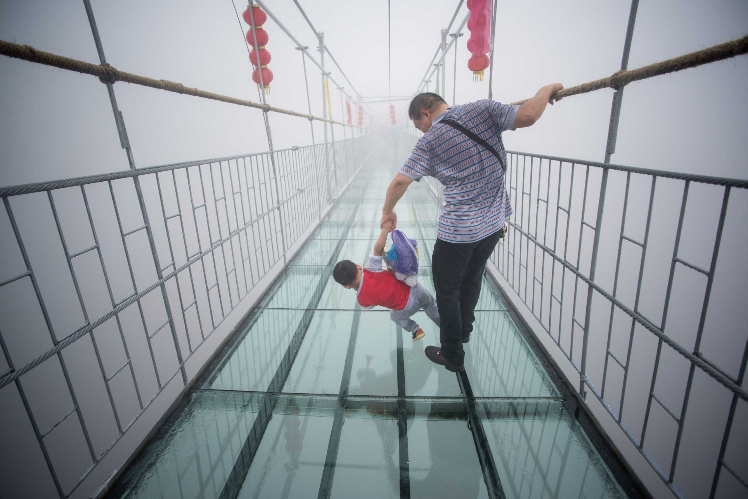 A Chinese tourist holds onto his son as they walk across a glass-bottomed suspension bridge in the Shinuizhai mountains in Pingjang county, Hunan province some 150 kilometers from Changsha on Oct. 7, 2015.