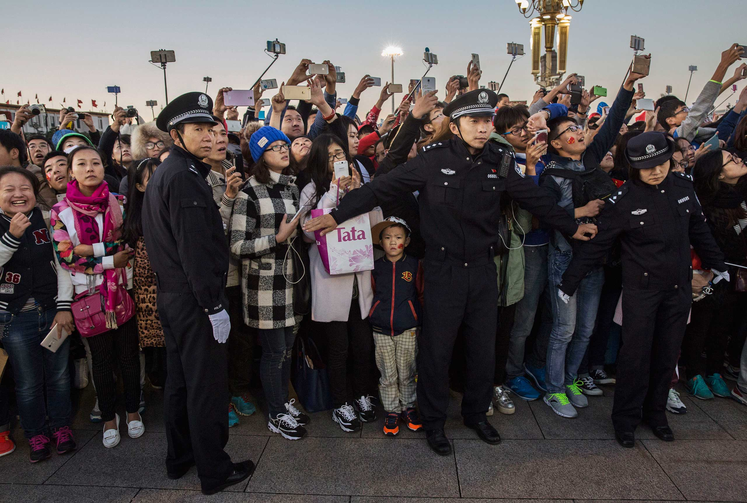 Police officers hold back crowds as they gather at the official flag raising ceremony at Tiananmen Square to mark the 66th National Day in Beijing, on Oct. 1, 2015.