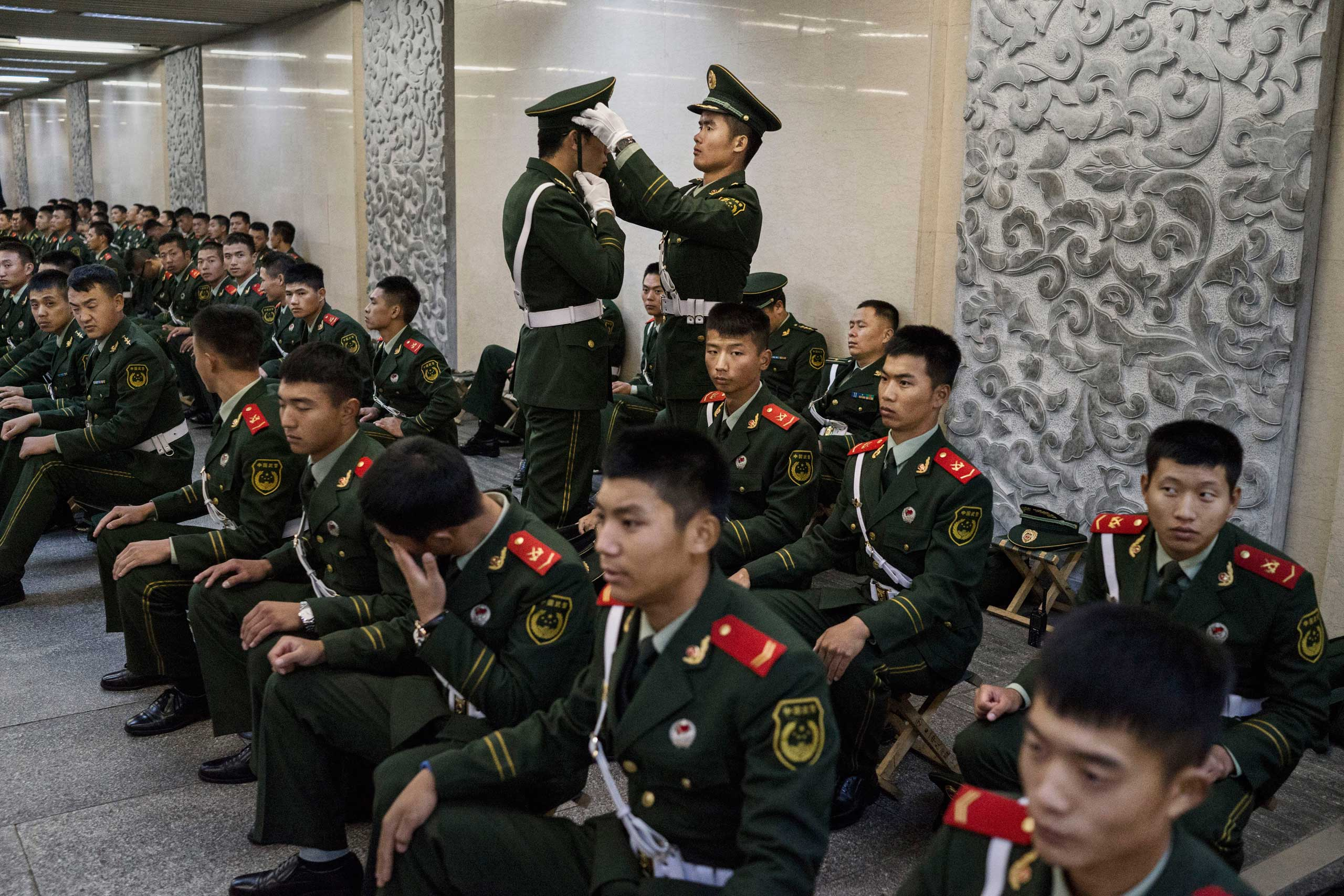 A paramilitary police officer adjusts another's cap as they and others wait in an underground tunnel before securing the official flag raising ceremony at Tiananmen Square to mark the 66th National Day in Beijing,  early on Oct. 1, 2015.
