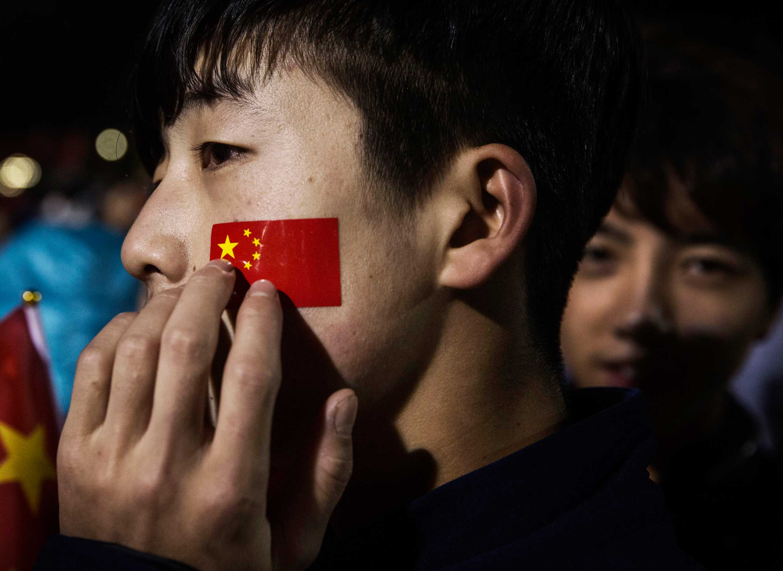 A man touches a flag sticker on his cheek while attending the official flag raising ceremony at Tiananmen Square to mark the 66th National Day in Beijing, on Oct. 1, 2015.