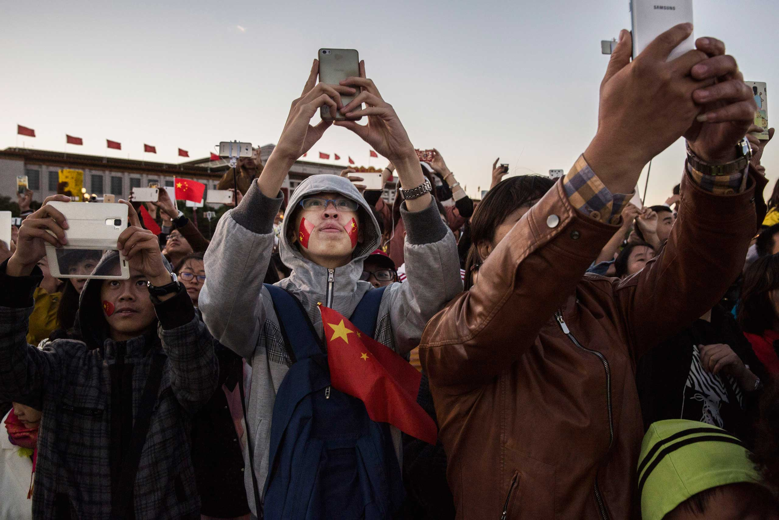 People take pictures as they gather during the official flag raising ceremony at Tiananmen Square to mark the 66th National Day in Beijing, on Oct. 1, 2015.