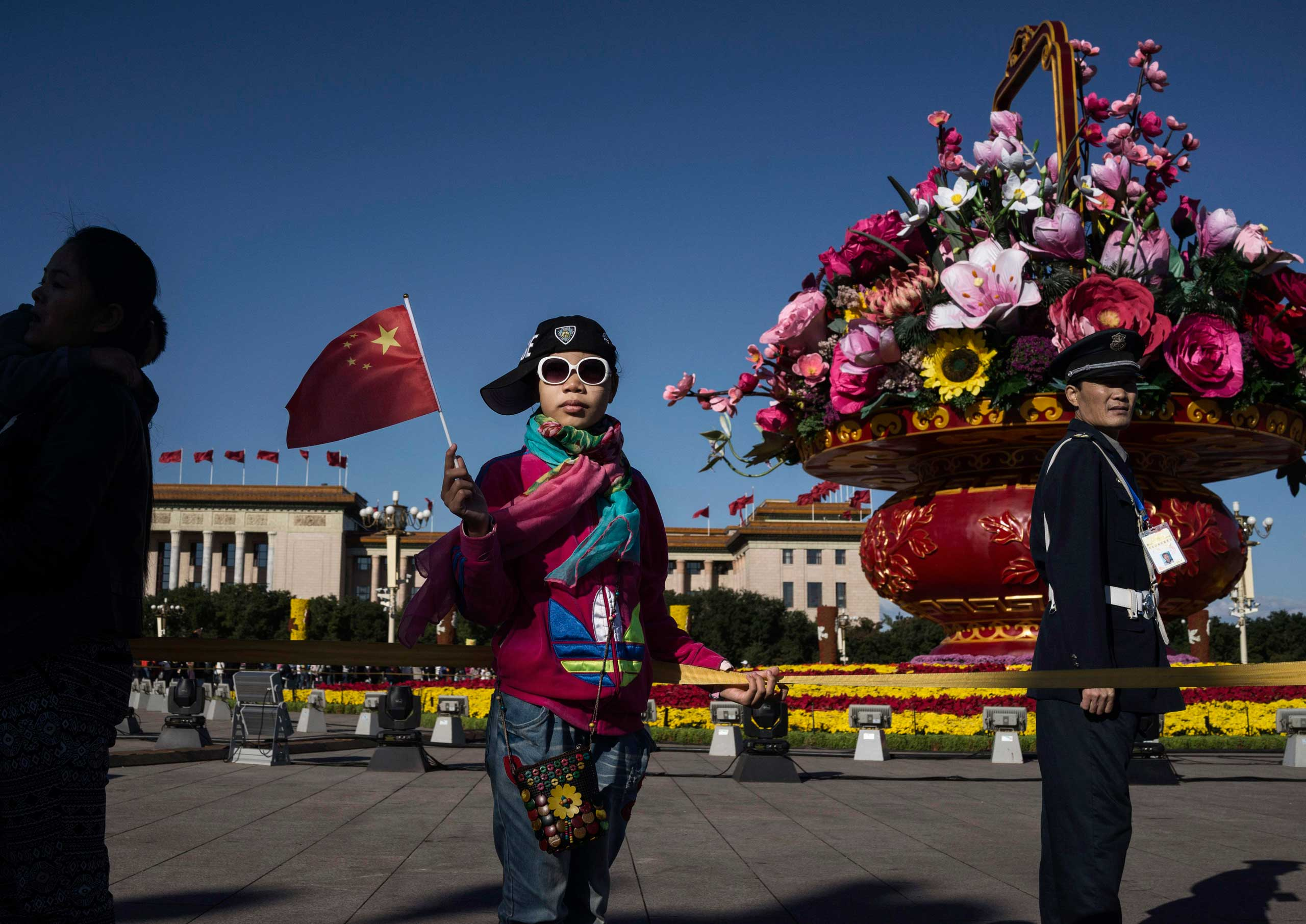 A girl poses in front of a large decorative flower arrangement after the official flag raising ceremony at Tiananmen Square to mark the 66th National Day in Beijing, on Oct. 1, 2015.