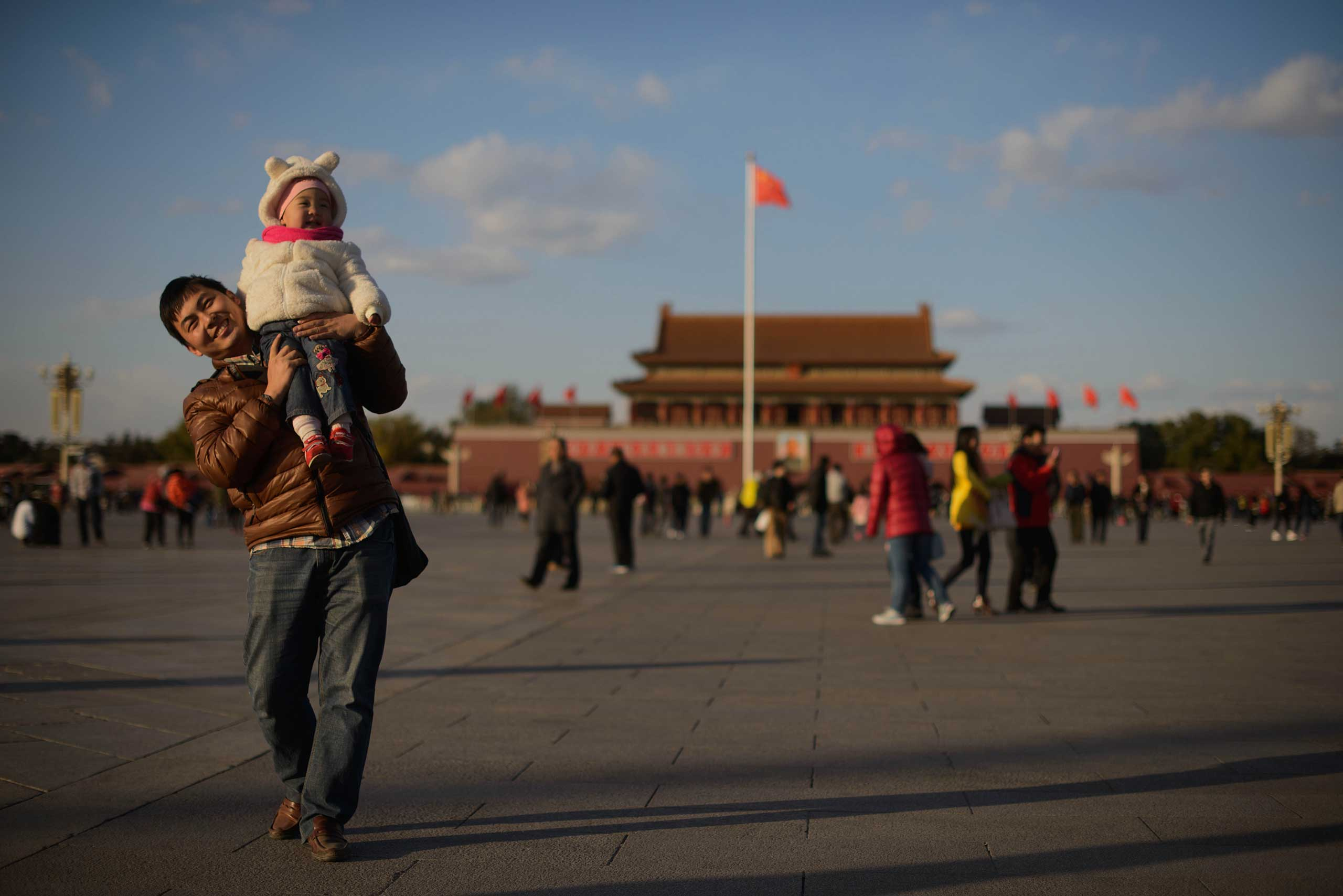 A man and child walk on Tiananmen Square in Beijing in 2013.