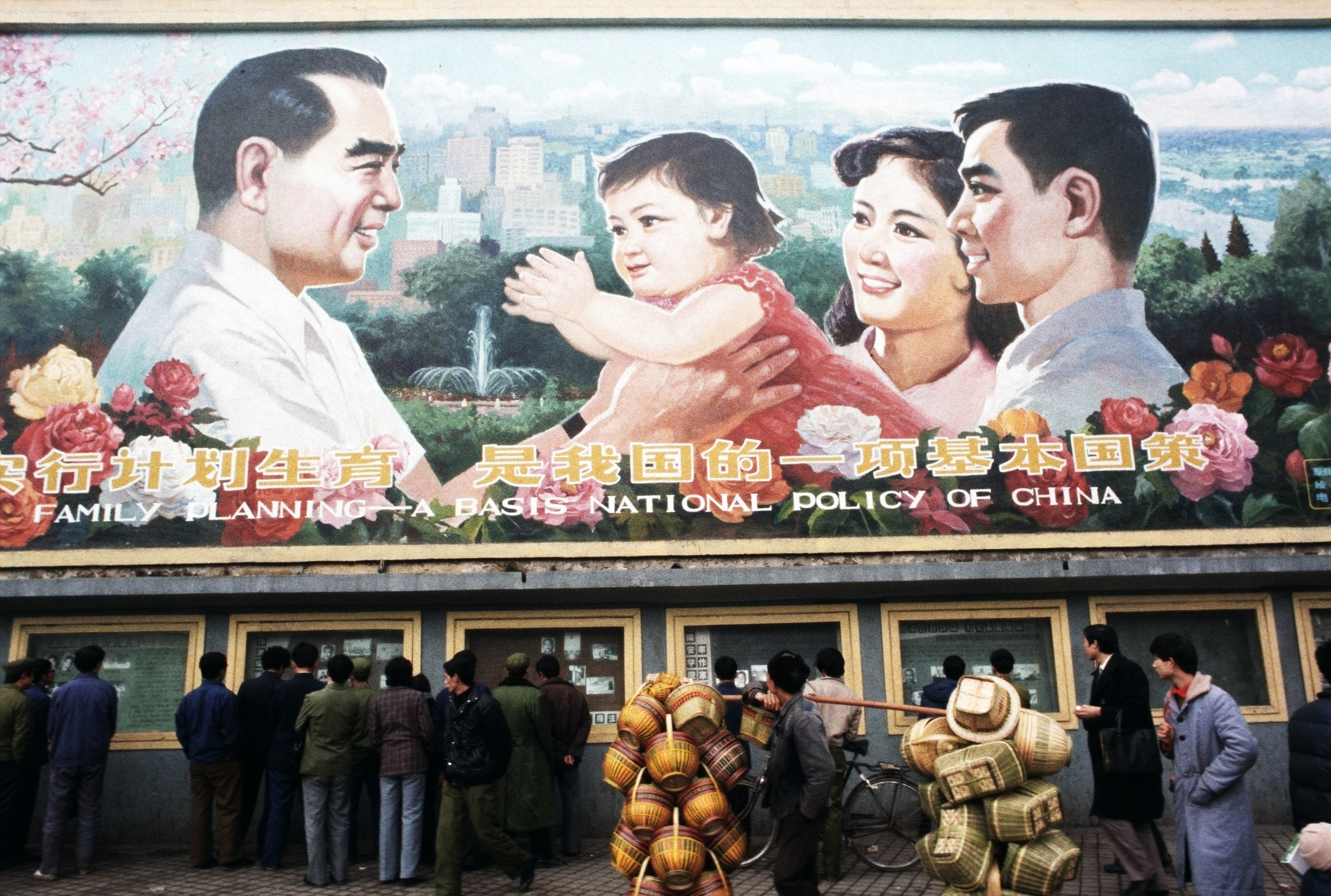 Pedestrians and a man carrying baskets pass by a huge billboard extolling the virtues of China's  One Child Family  policy.