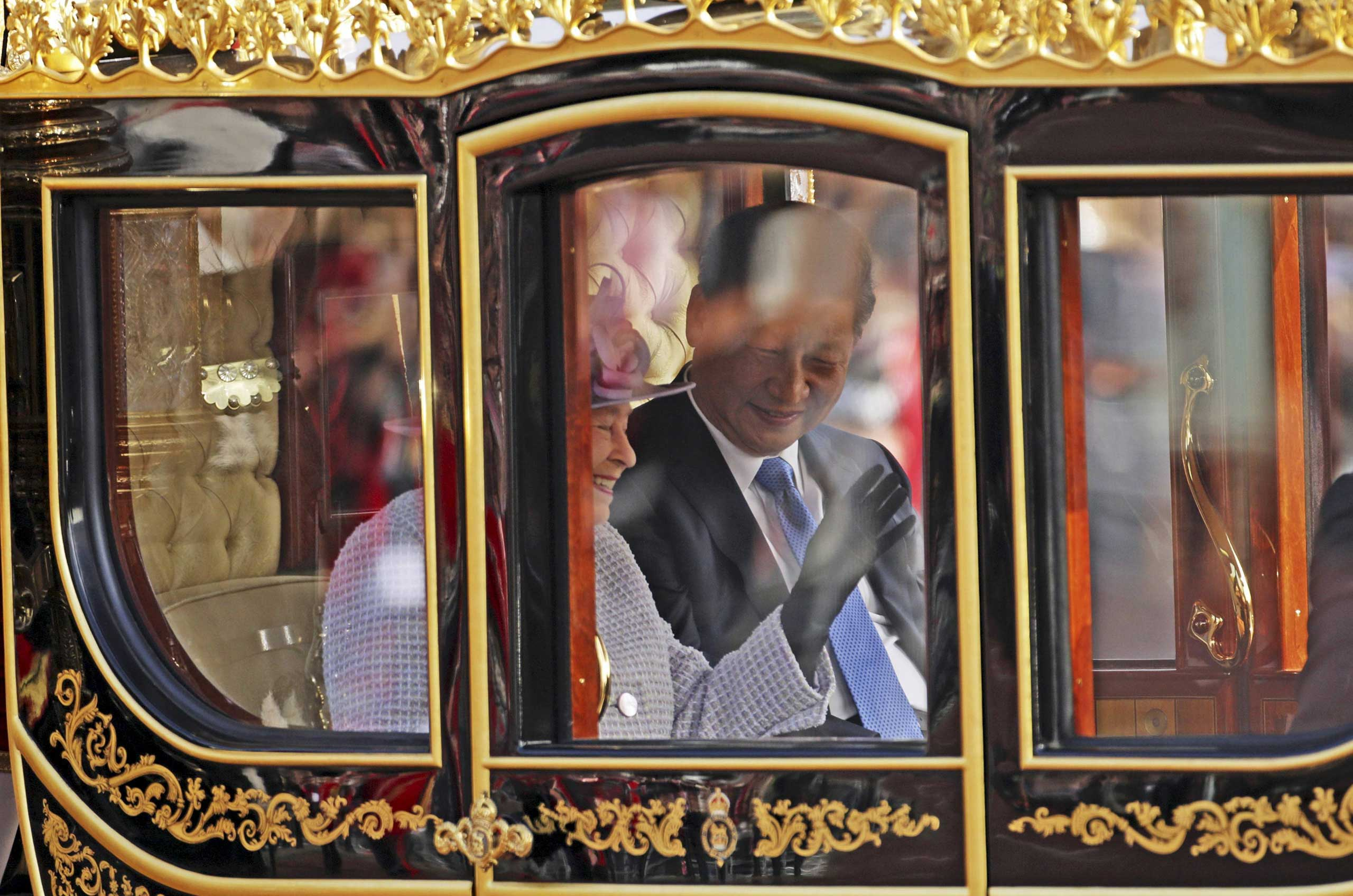 Queen Elizabeth and President Xi Jinping, are driven by carriage along The Mall to Buckingham Palace in London, Oct. 20, 2015.