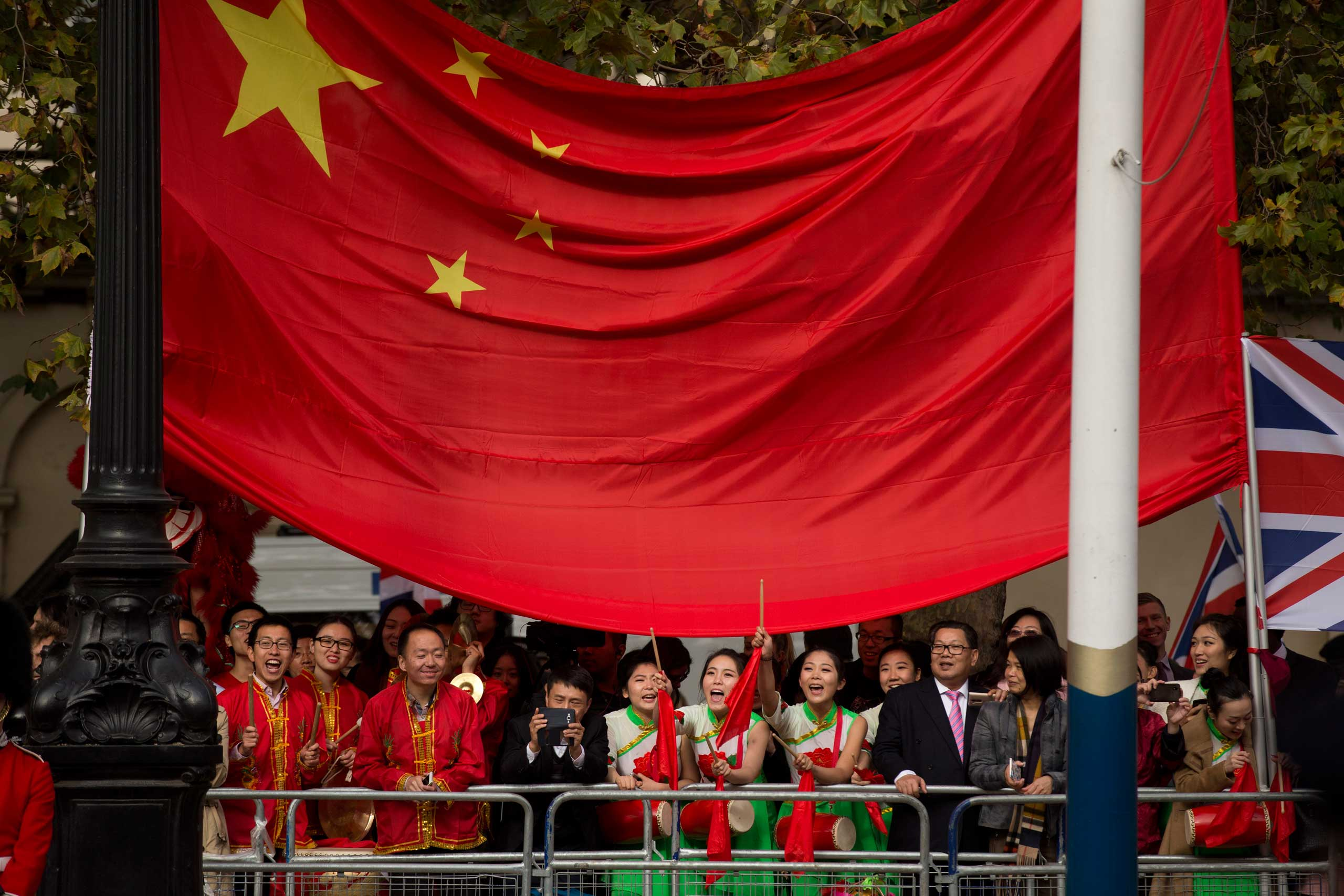 Supporters of President Xi stand under a large Chinese flag before the President passes by on a horse-drawn carriage with Britain's Queen Elizabeth II on the Mall en route to Buckingham Palace in London,  Oct. 20, 2015.