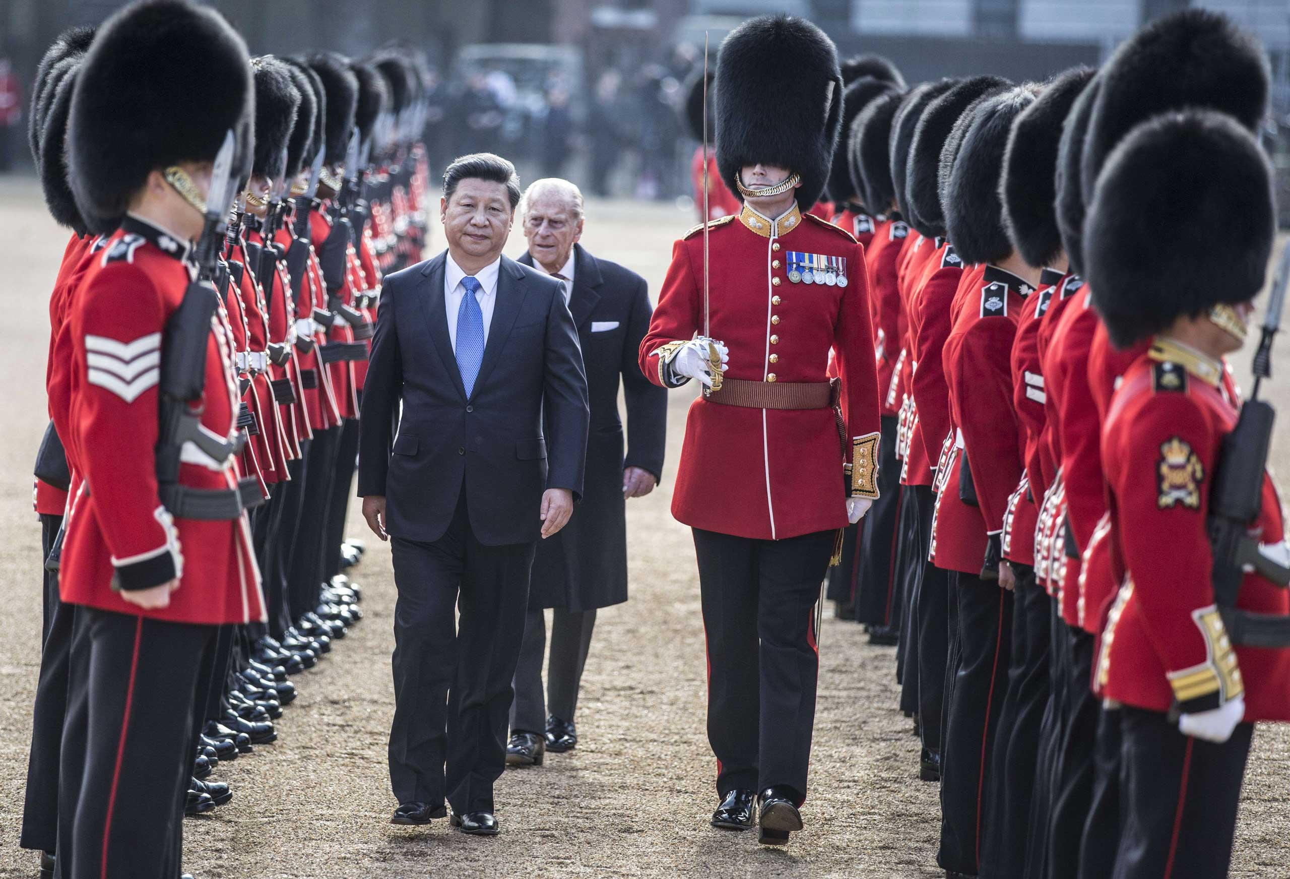 President Xi Jinping and Britain's Prince Philip, Duke of Edinburgh inspect the guard of honor on Horse Guards Parade in central London during the ceremonial welcome on the first official day of a state visit, on Oct. 20, 2015.
