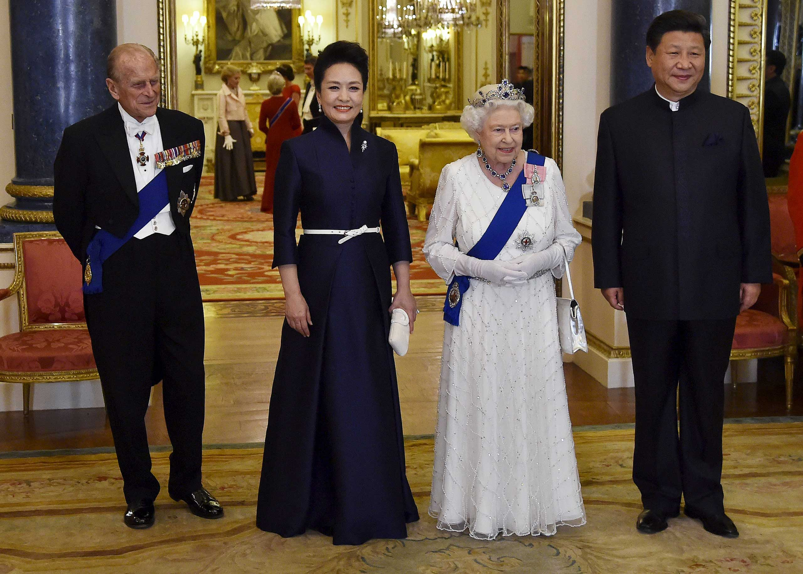 President Xi Jinping and his wife Peng Liyuan accompany Britain's Queen Elizabeth II and her husband Prince Philip, Duke of Edinburgh, as they arrive for a state banquet at Buckingham Palace, in London, on Oct. 20,2015.