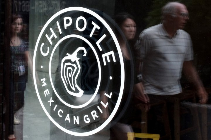 People pass walk by a Chipotle Restaurant in New York City on Sept. 11, 2015.