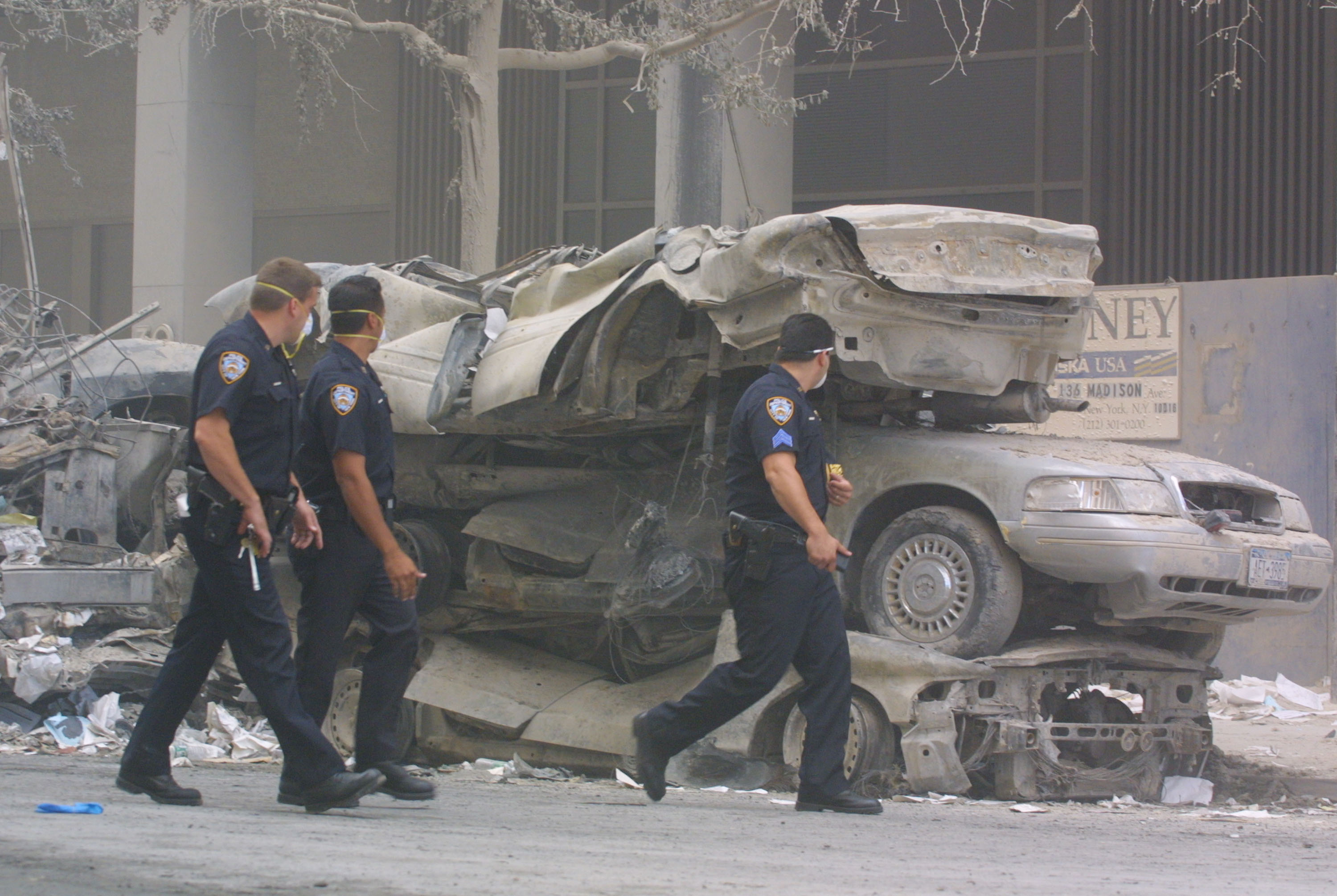 Policemen walk past crushed cars near the wreckage of the World Trade Center on Sept. 13, 2001 in New York City.