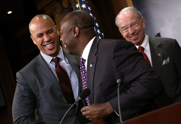 Sen. Corey Booker (L) (D-NJ) hugs Sen. Tim Scott (C) (R-SC) as Senate Judiciary Committee Chairman Sen. Chuck Grassley (R) (R-IA) looks on during a press conference at the U.S. Capitol announcing a bipartisan effort to reform the criminal justice system in Washington, DC., Oct. 1, 2015.