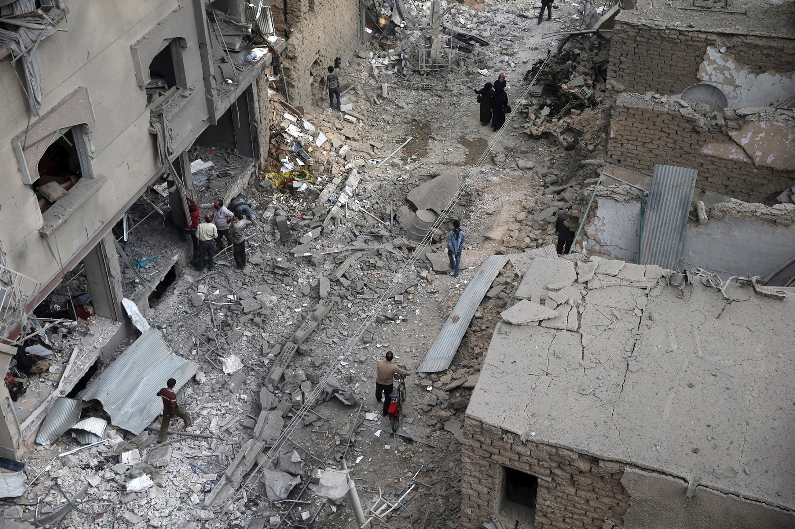Residents inspect damage from what activists said was an airstrike by forces loyal to Syria's President Bashar al-Assad on the main field hospital in the town of Douma, north-east of Damascus, on Oct. 29, 2015.