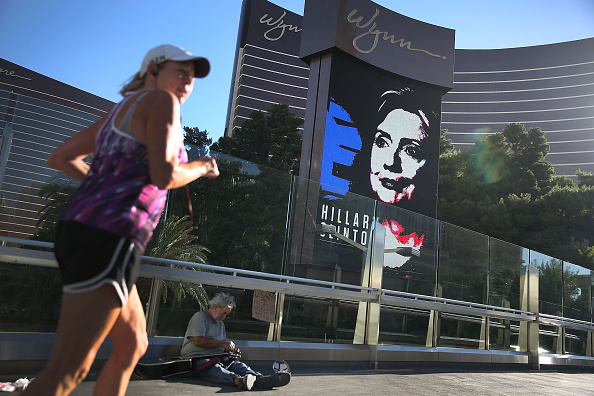Michael McLean sets up to play his guitar for money near a billboard showing a picture of Democratic Presidential candidate Hillary Clinton advertising the upcoming Democratic Presidential debate at the Wynn Las Vegas resort and casino on October 12, 2015 in Las Vegas, Nevada.