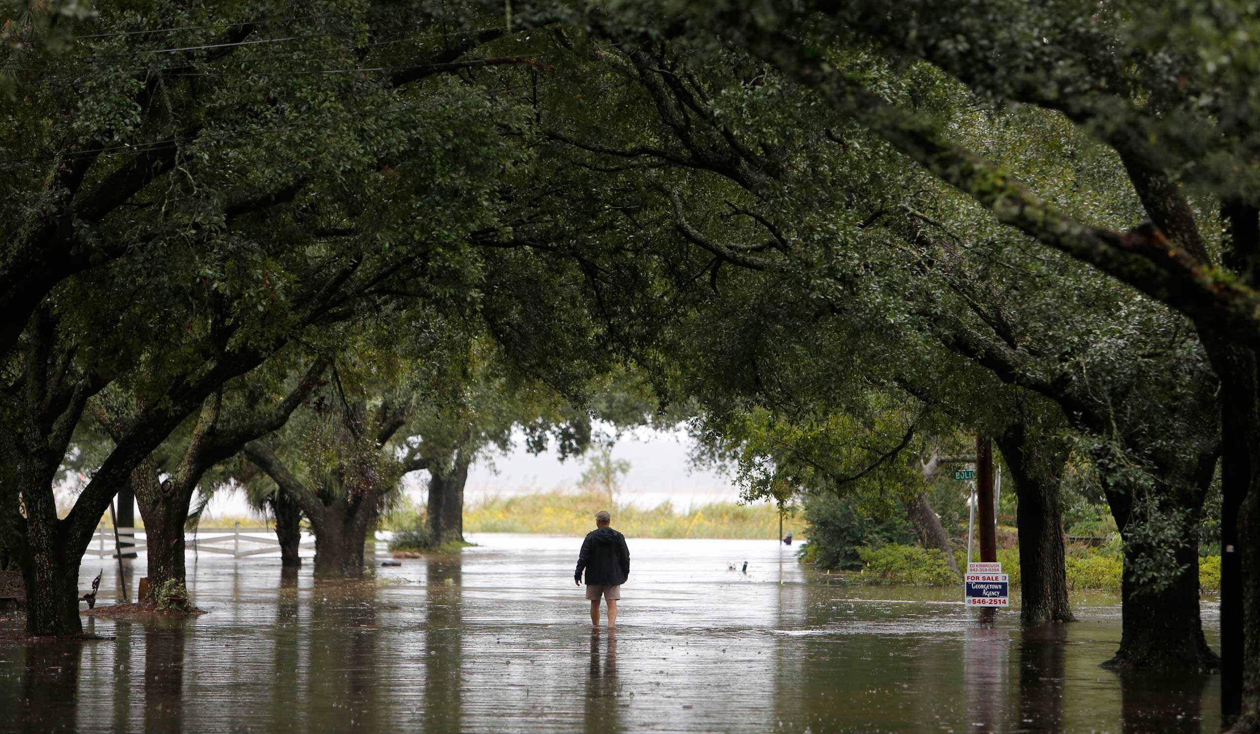 A resident walks down a flooded Prince St. in Georgetown, S.C., Oct. 4, 2015.