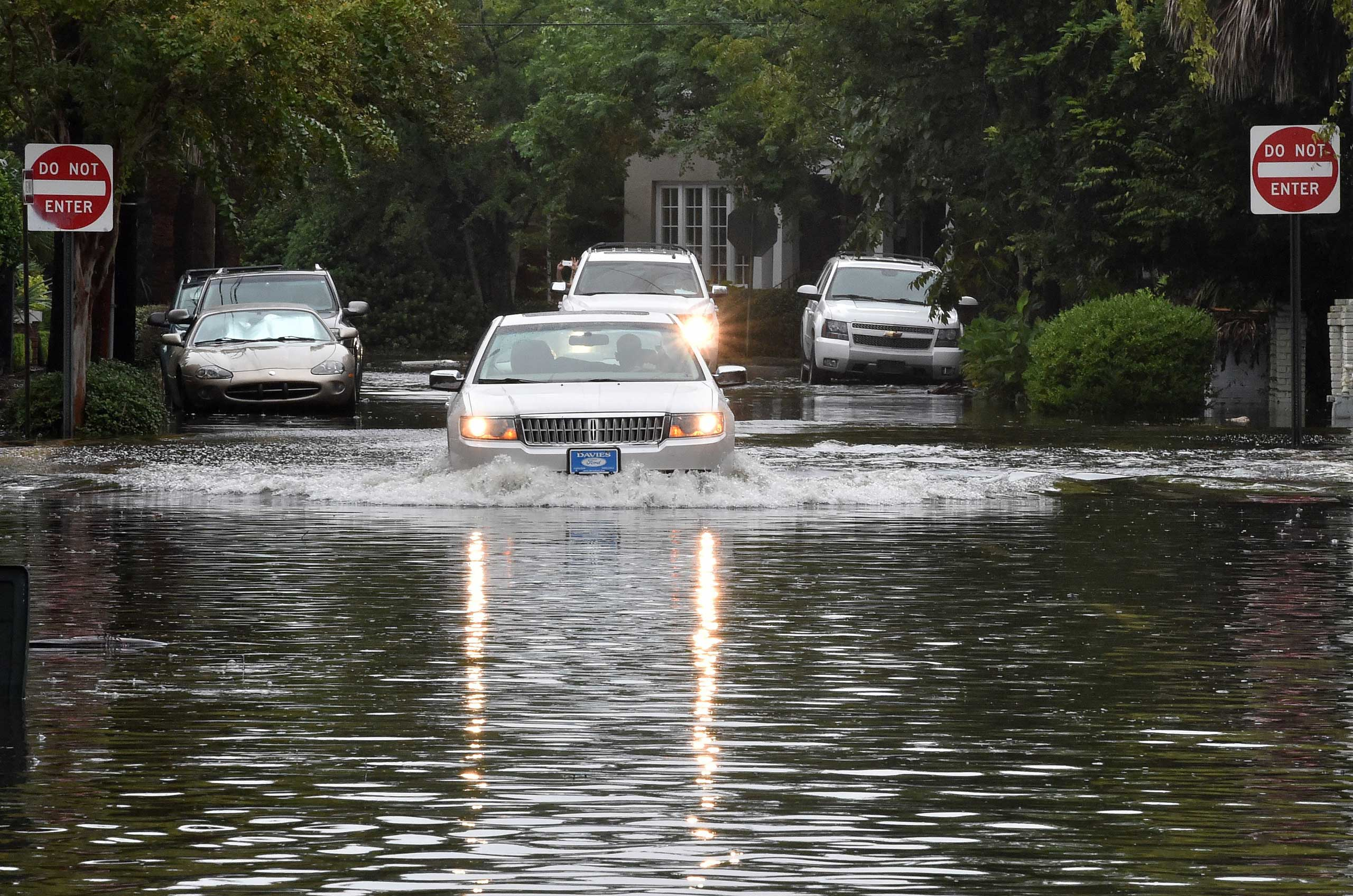 A car drives down a flooded street in Charleston, S.C., on Oct. 4, 2015.