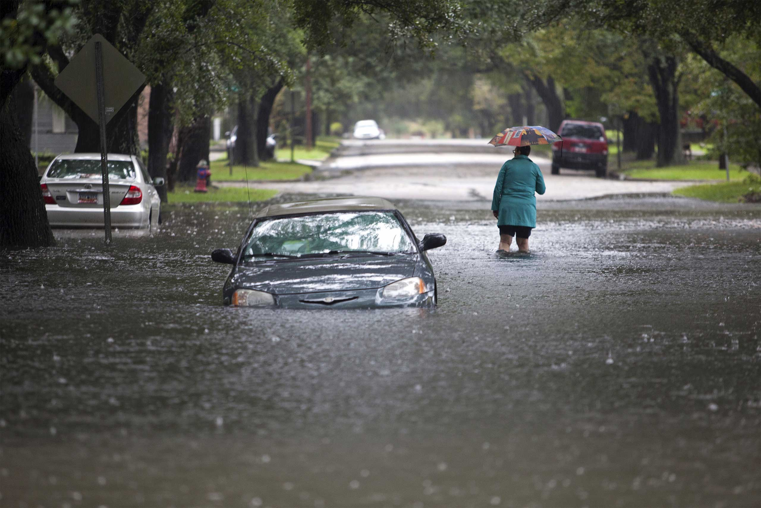 Clare Reigard of Georgetown, South Carolina, abandons her car after it stalled on Duke Street due to heavy rains in Georgetown, S.C., Oct. 4, 2015.