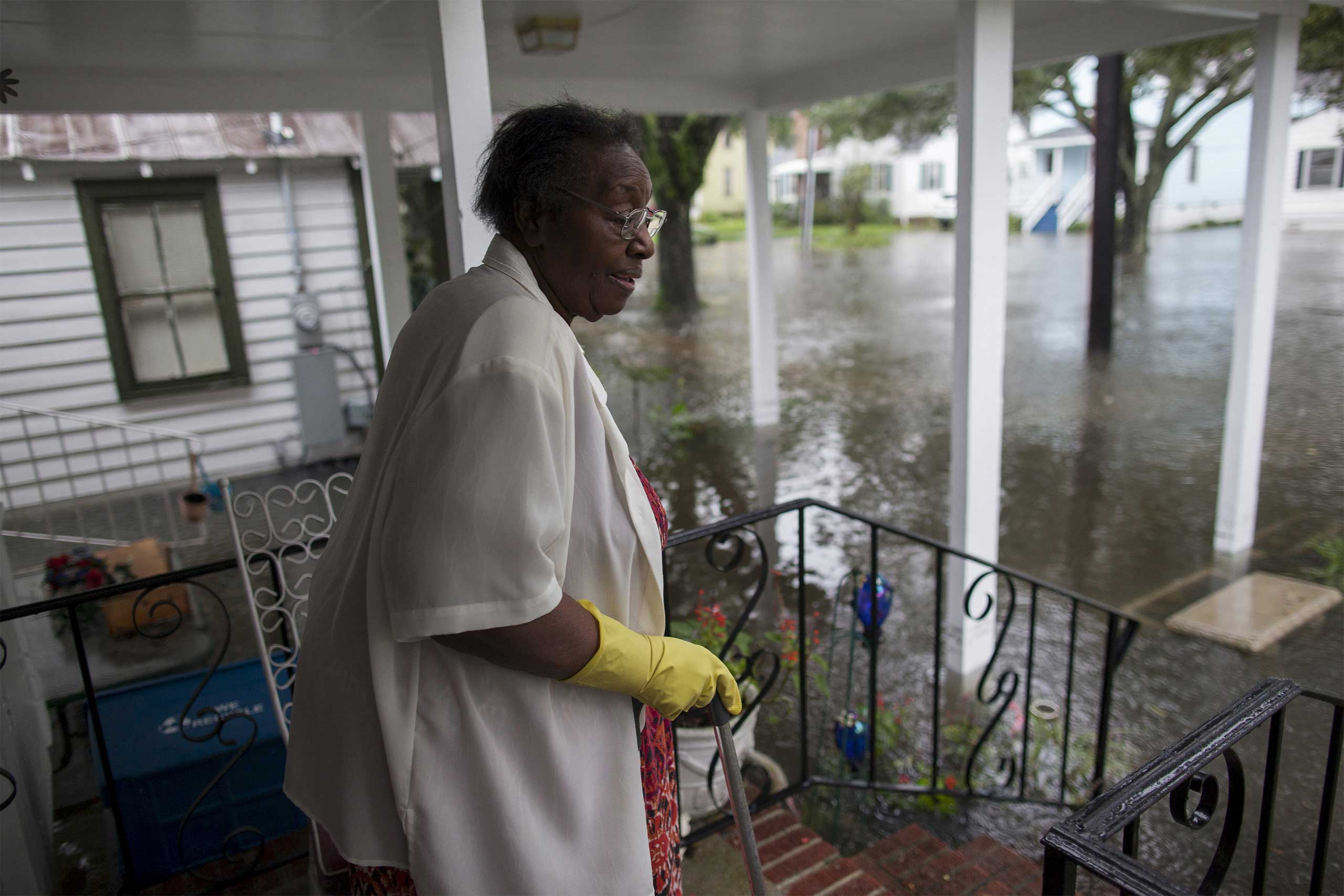 Ammie McKnight watches the level of floodwaters in the front yard of her Orange Street home in Georgetown, S.C., Oct. 4, 2015.