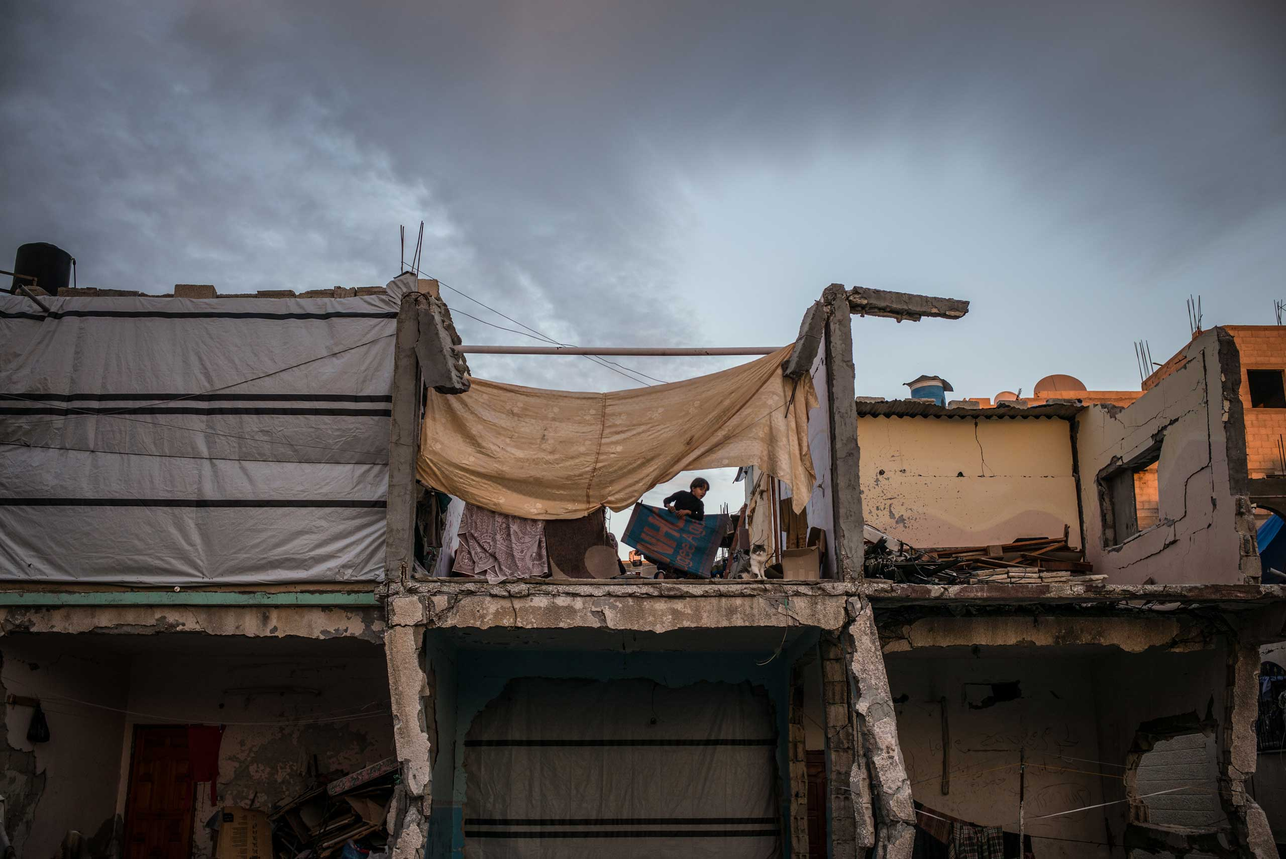 A child is seen in her ravaged house in Khuza'a, in the south of the Gaza Strip. Families are trying to go back to live in their houses. The Gaza Strip, December 2014.