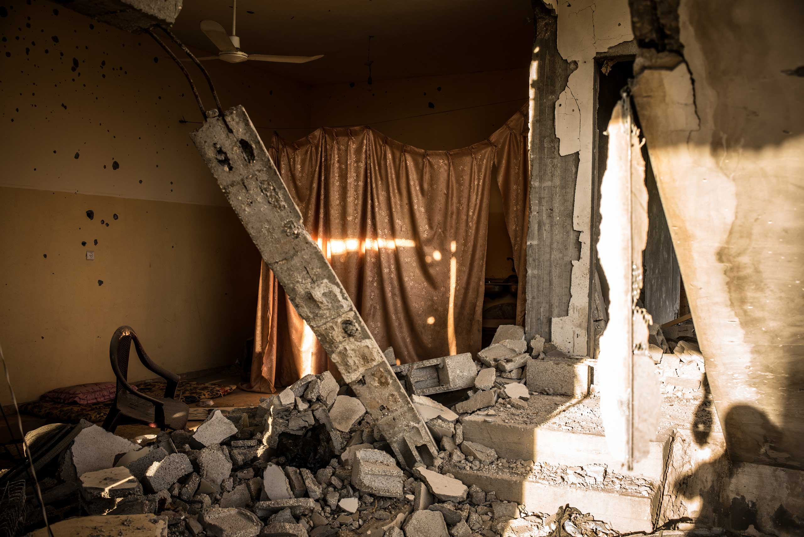 A gutted kitchen in one of the destroyed buildings in Khan Yunis, in the southeast of the Gaza Strip. Blankets are used to create some privacy. The Gaza Strip, December 2014.
