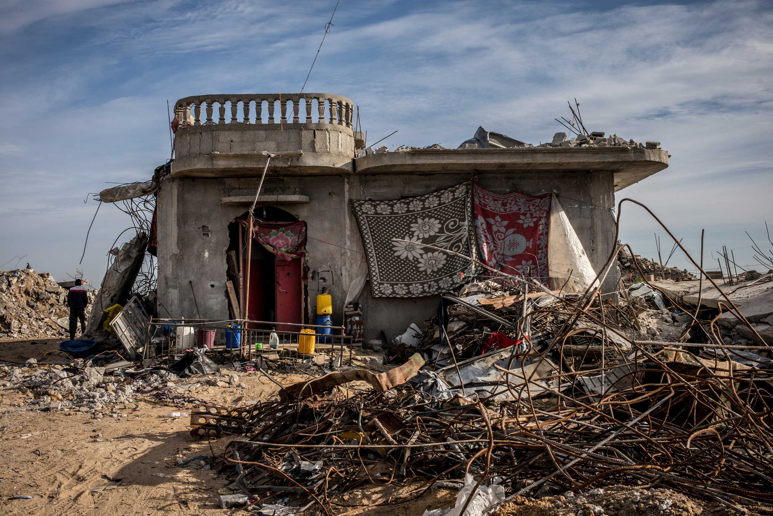A house resisted the shelling in the Khuza'a area, in the southern Gaza Strip. Colorful blankets cover the wall and part of the entrance. The Gaza Strip, December 2014.