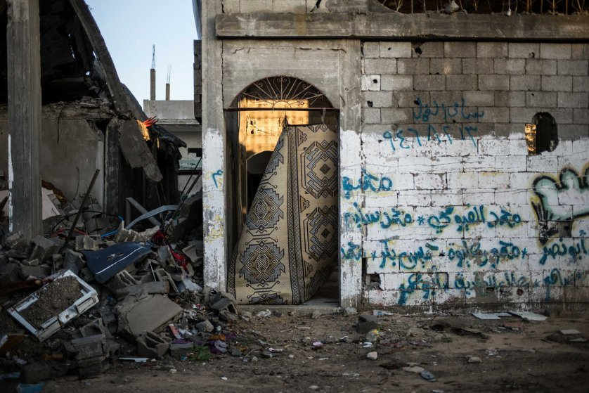 A blanket replaces a missing door in a destroyed building where recycled materials are stocked, in the northern Gaza Strip town of Beit Hanoun. December 2014.