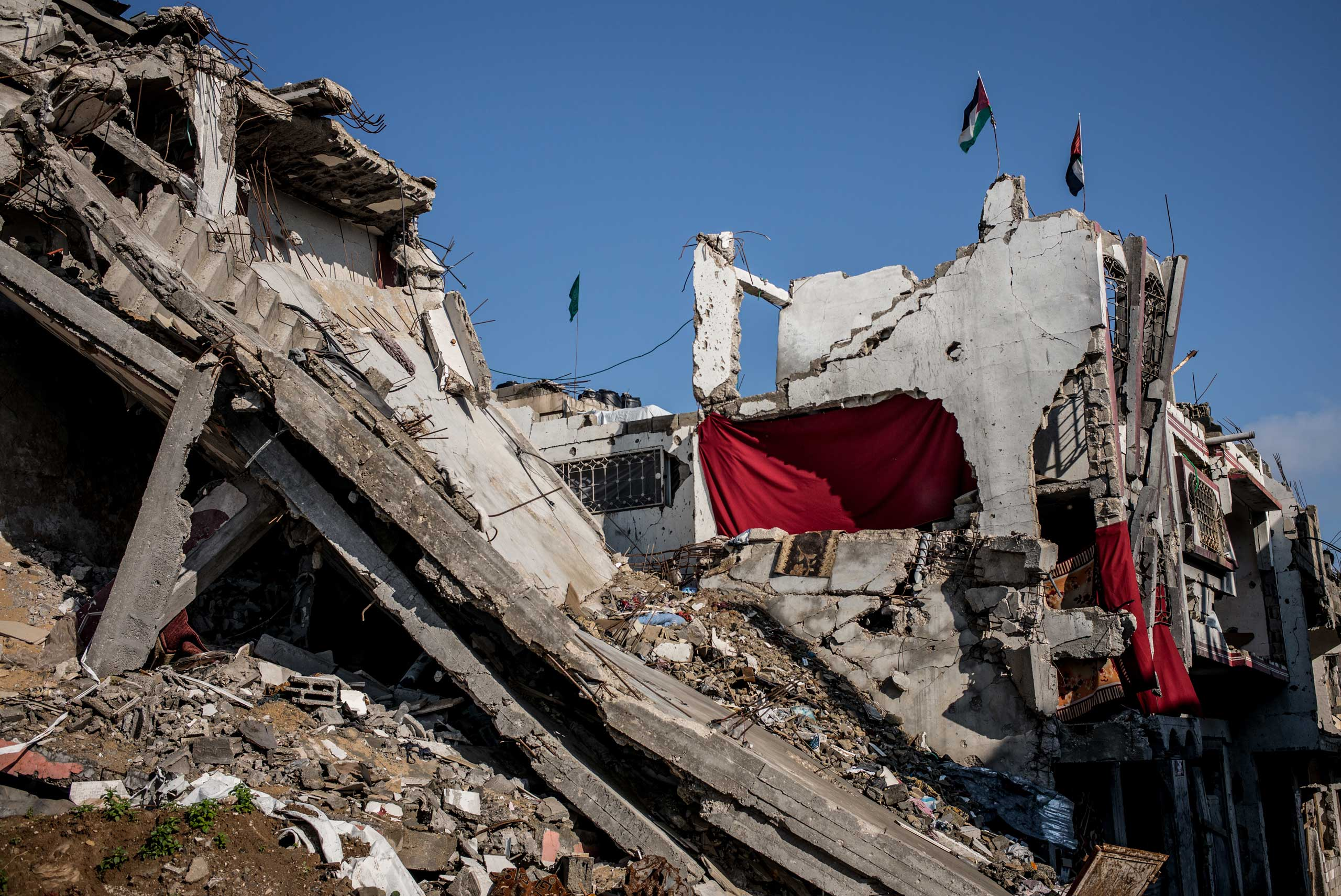 In a partially destroyed building in Shejaiya, Gaza, red blankets are used to replace the missing walls. Two Palestinian flags and a Hamas one stand on the top of the building. The Gaza Strip, December 2014.
