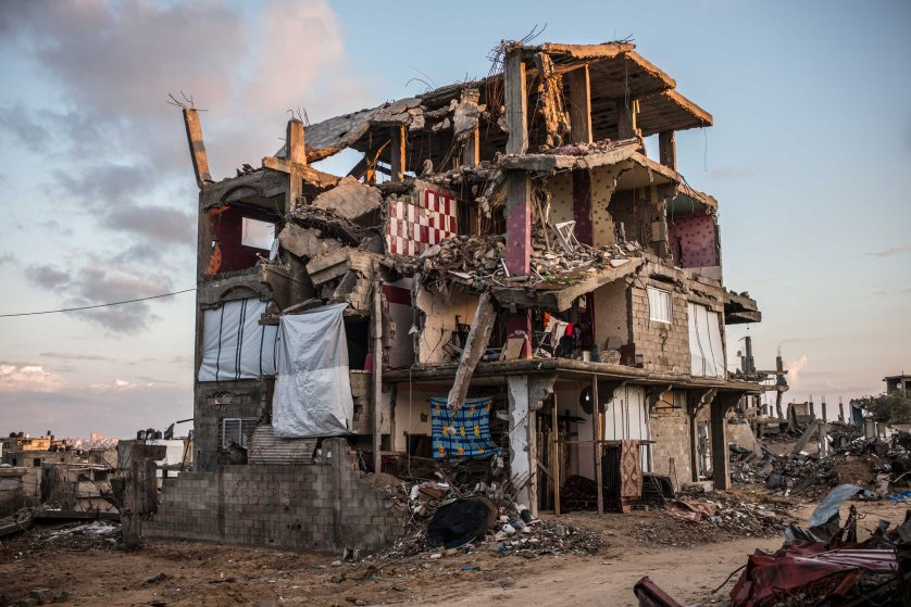 A partially destroyed building in Shejaiya, a neighborhood district of the Palestinian city of Gaza. Some family tried to replace the missing walls of their apartments with blankets. Shejaiya, Gaza. December 2014.