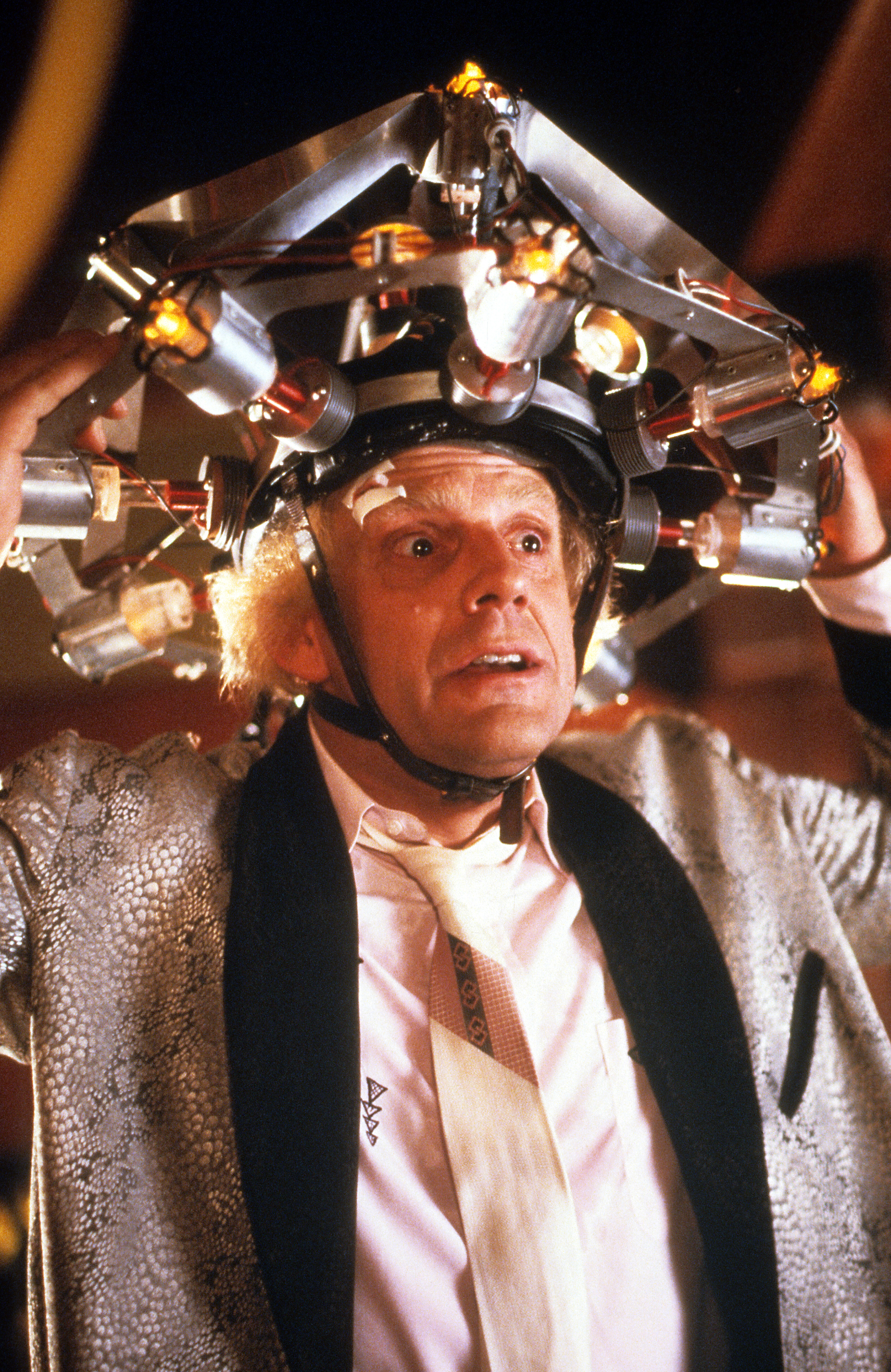 Christopher Lloyd wearing concoction on his head in a scene from the film 'Back To The Future', 1985